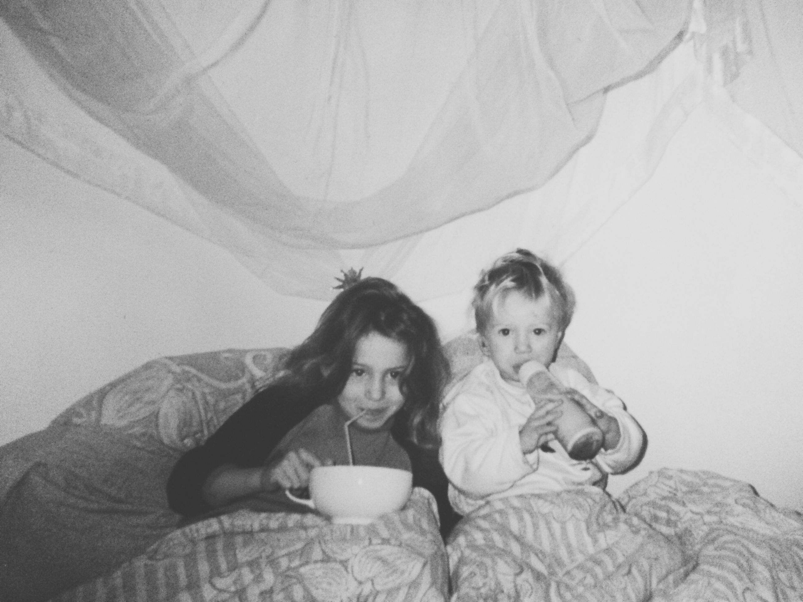 childhood, girls, togetherness, two people, indoors, food and drink, leisure activity, looking at camera, lifestyles, holding, elementary age, drink, sibling, bed, portrait, bonding, real people, young women, young adult, bedroom, day, people