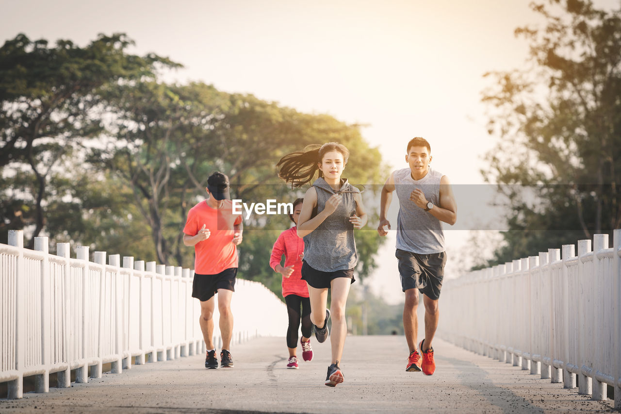 lifestyles, real people, exercising, men, togetherness, women, running, nature, footpath, group of people, healthy lifestyle, males, sport, bridge, leisure activity, day, adult, jogging, bridge - man made structure, clothing, outdoors