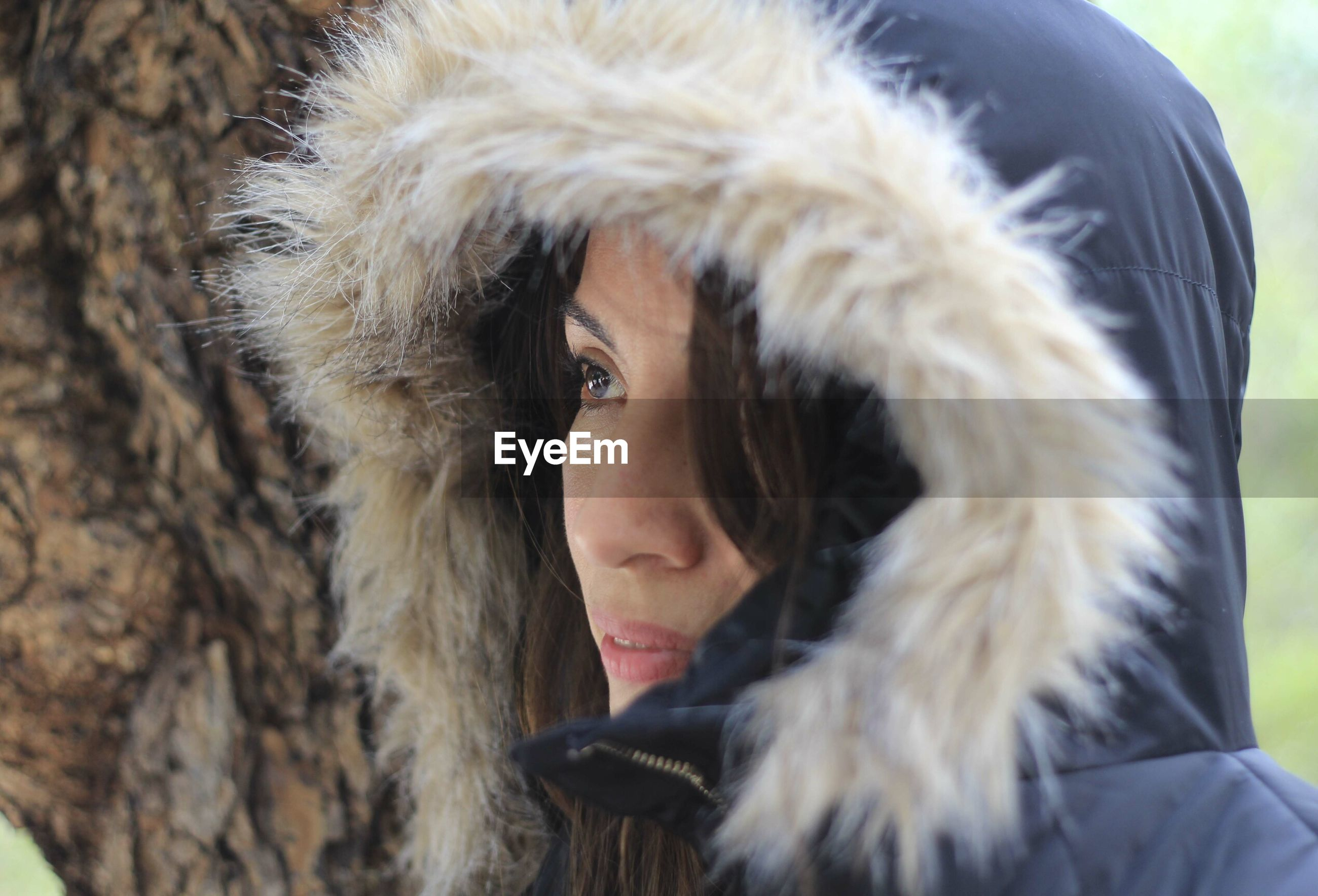 Close-up of thoughtful woman in fur coat by tree trunk