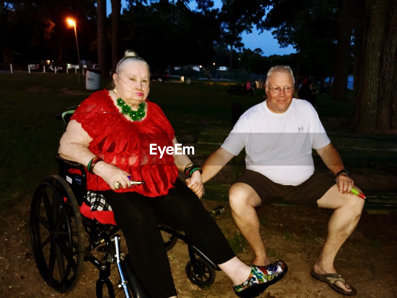 Senior man with mother sitting on wheelchair at park