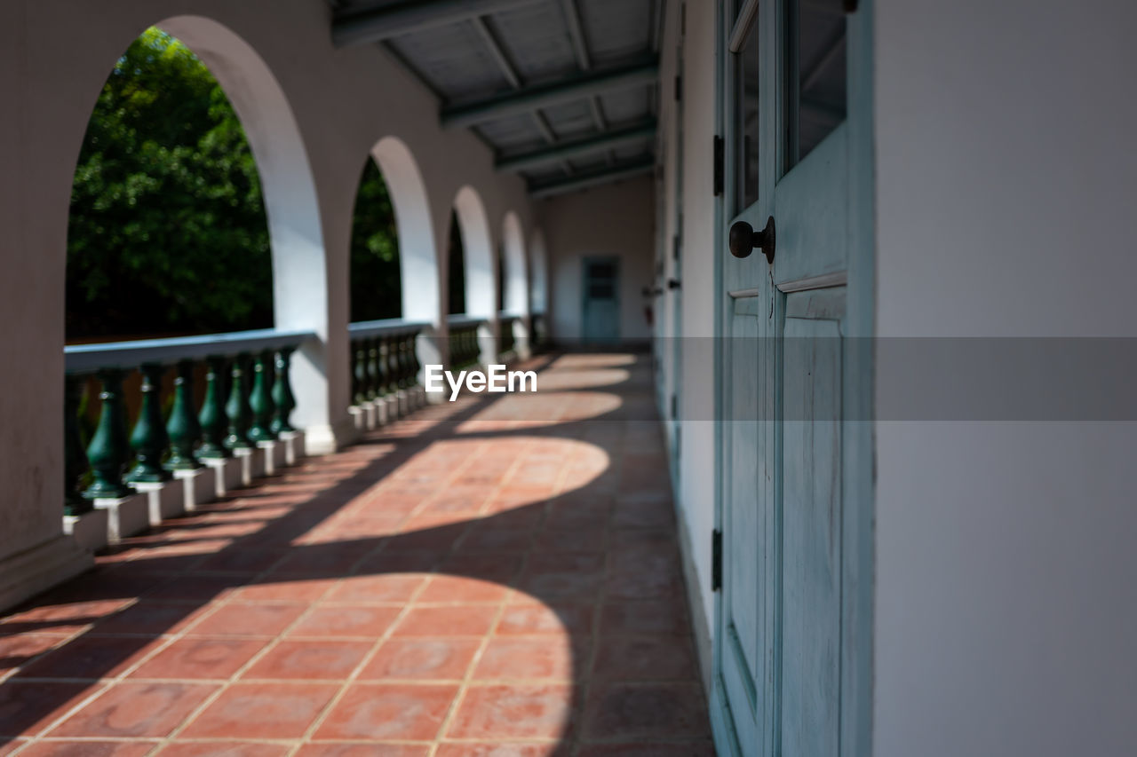 arch, architecture, built structure, arcade, day, building, sunlight, corridor, no people, architectural column, building exterior, nature, in a row, shadow, railing, entrance, outdoors, flooring, door, direction, colonnade, tiled floor, balustrade