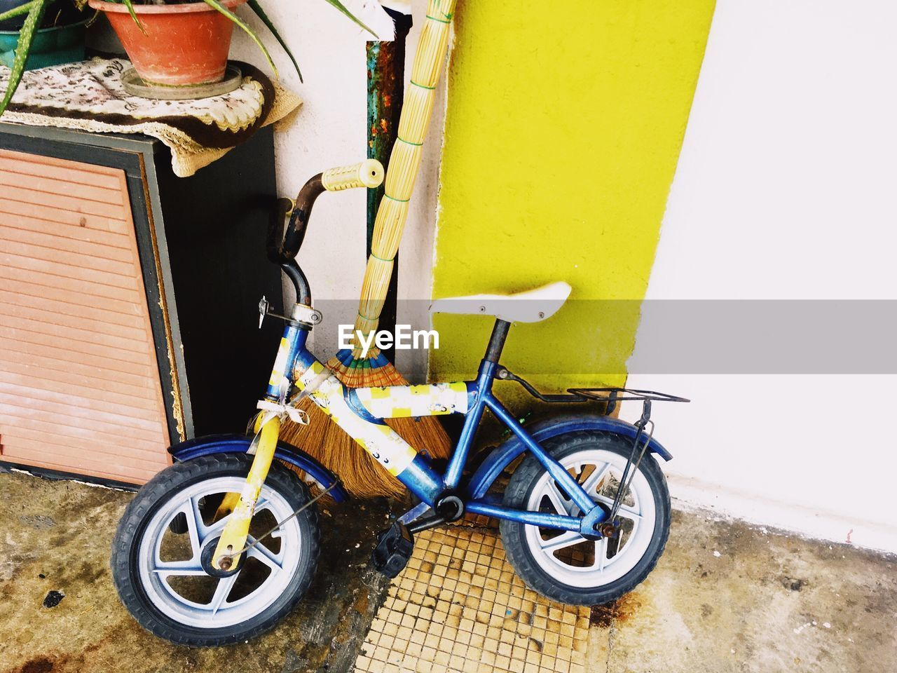 land vehicle, transportation, mode of transport, stationary, day, no people, outdoors, wheel, yellow, built structure, scooter, architecture, building exterior, tire