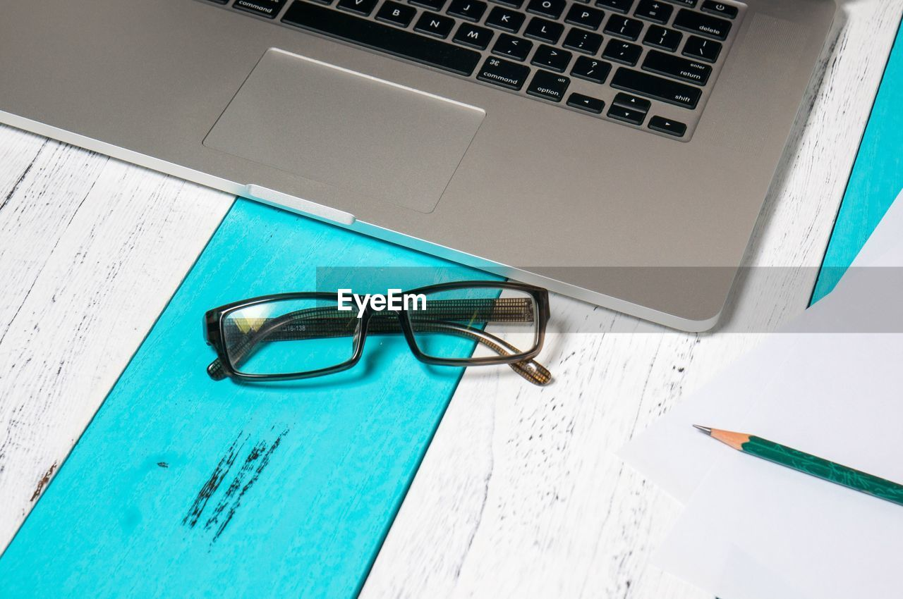 High Angle View Of Laptop With Eyeglasses On Desk
