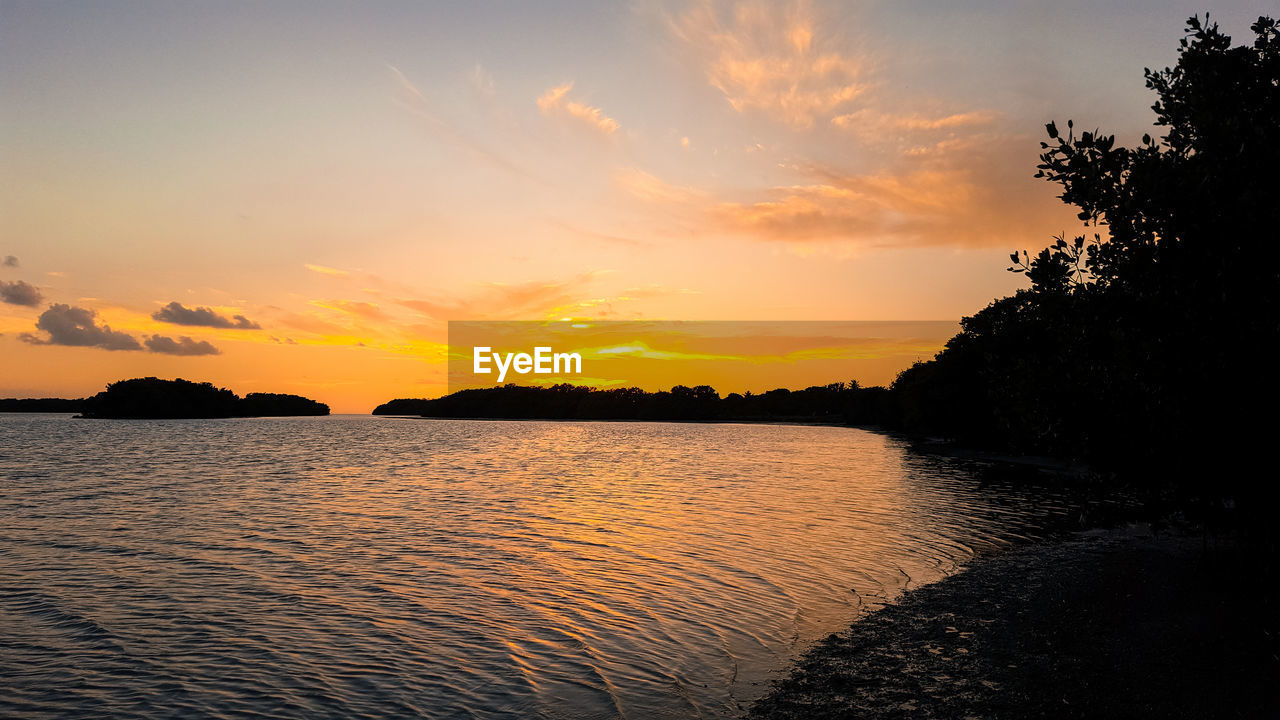 sunset, tranquil scene, water, tranquility, scenics, silhouette, beauty in nature, nature, tree, sky, orange color, no people, outdoors, sea, beach, day