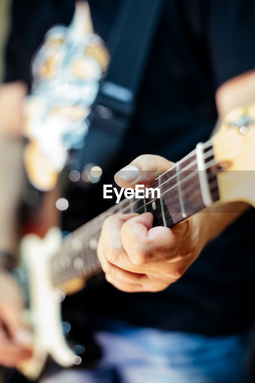 musical instrument, music, playing, string instrument, guitar, string, arts culture and entertainment, performance, musical equipment, musician, artist, guitarist, musical instrument string, holding, skill, plucking an instrument, real people, one person, electric guitar, men, acoustic guitar, hand, rock music, finger