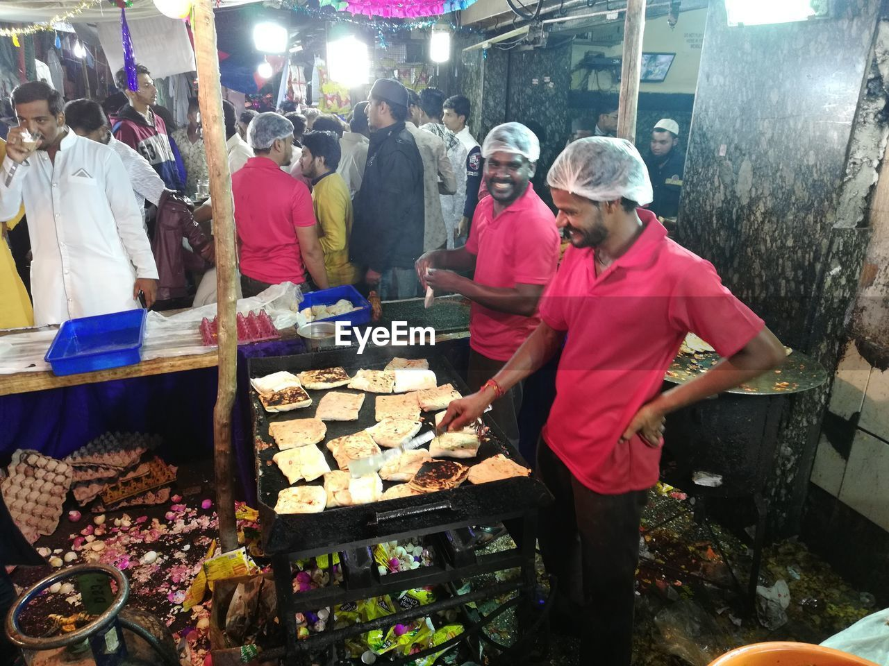 food, group of people, men, real people, food and drink, preparing food, market, occupation, people, preparation, adult, meat, standing, night, women, freshness, market stall, retail, business, lifestyles, outdoors, buying, chef