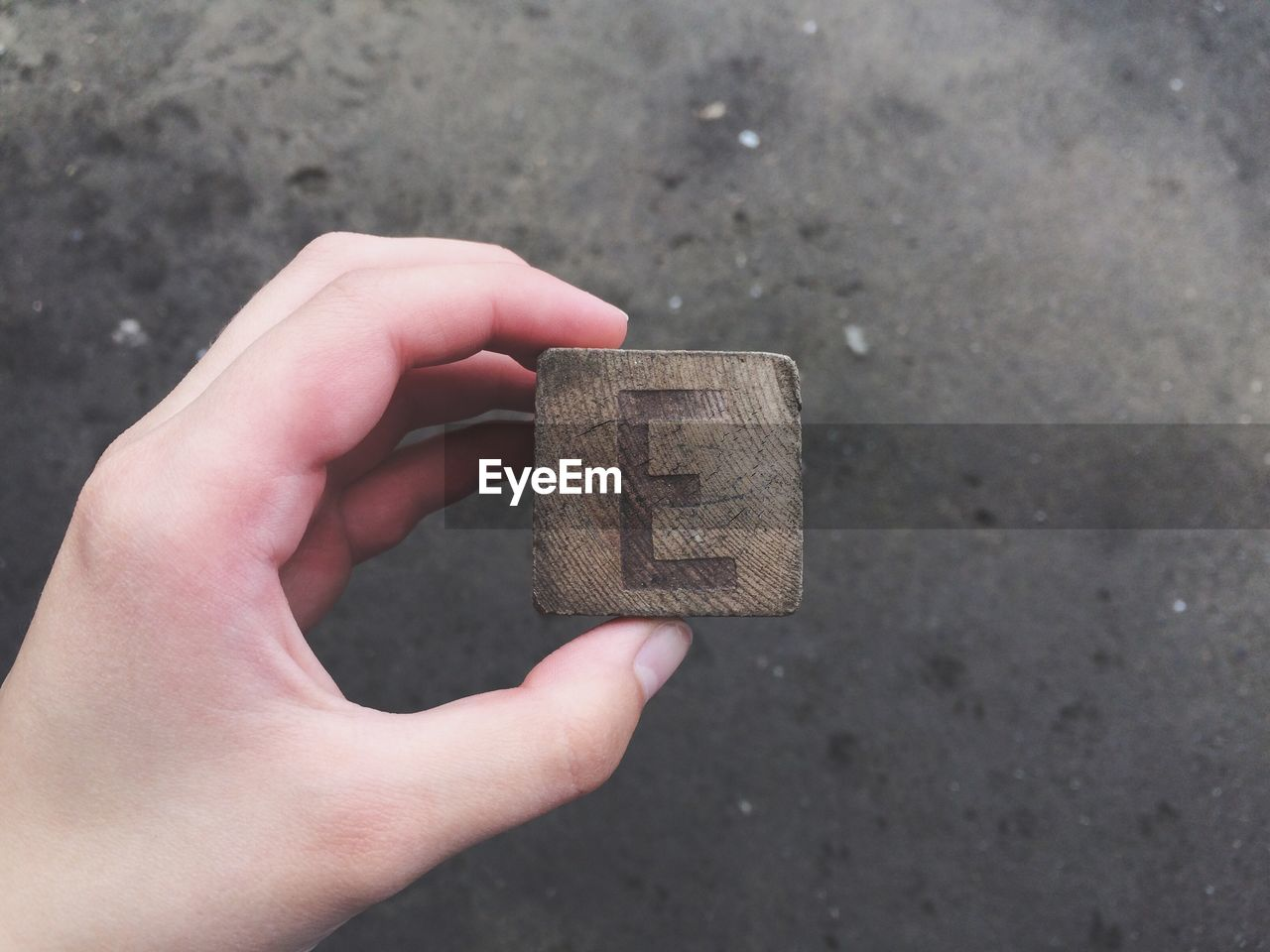 Close-Up Of Human Hand Holding Wooden Block
