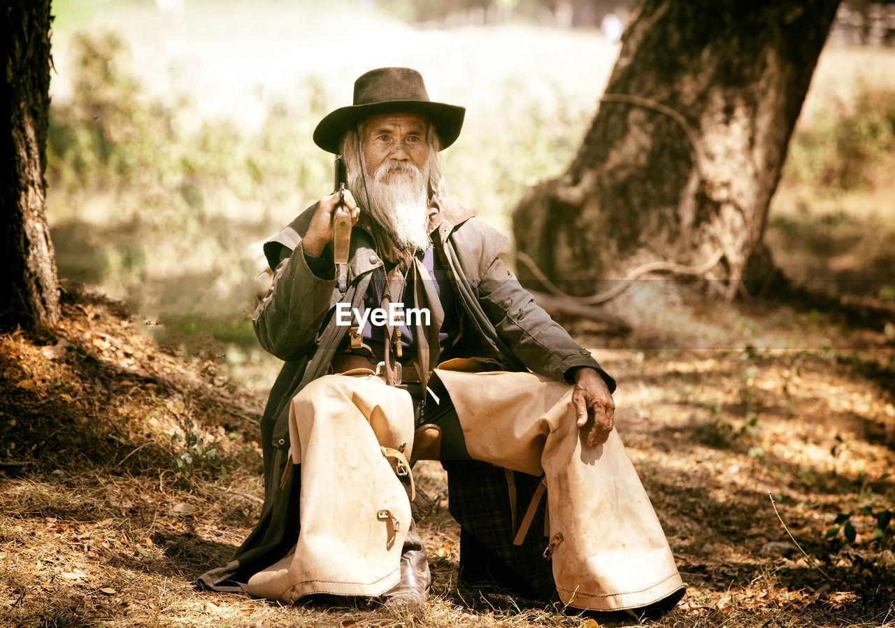 sitting, hat, real people, tree, one person, day, nature, clothing, land, full length, leisure activity, sunlight, focus on foreground, activity, plant, field, men, outdoors, relaxation, cowboy, mature men, cowboy hat