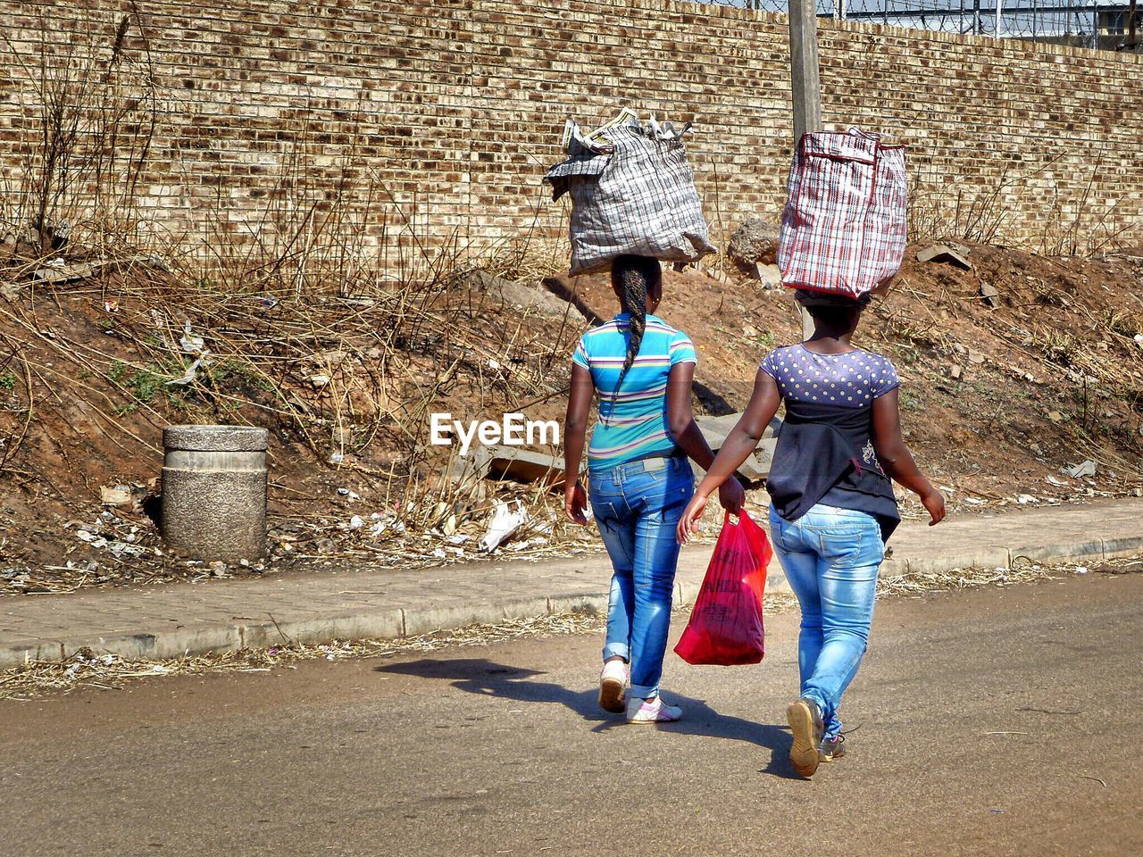 Rear View Of Women Carrying Bags On Head While Walking On Street