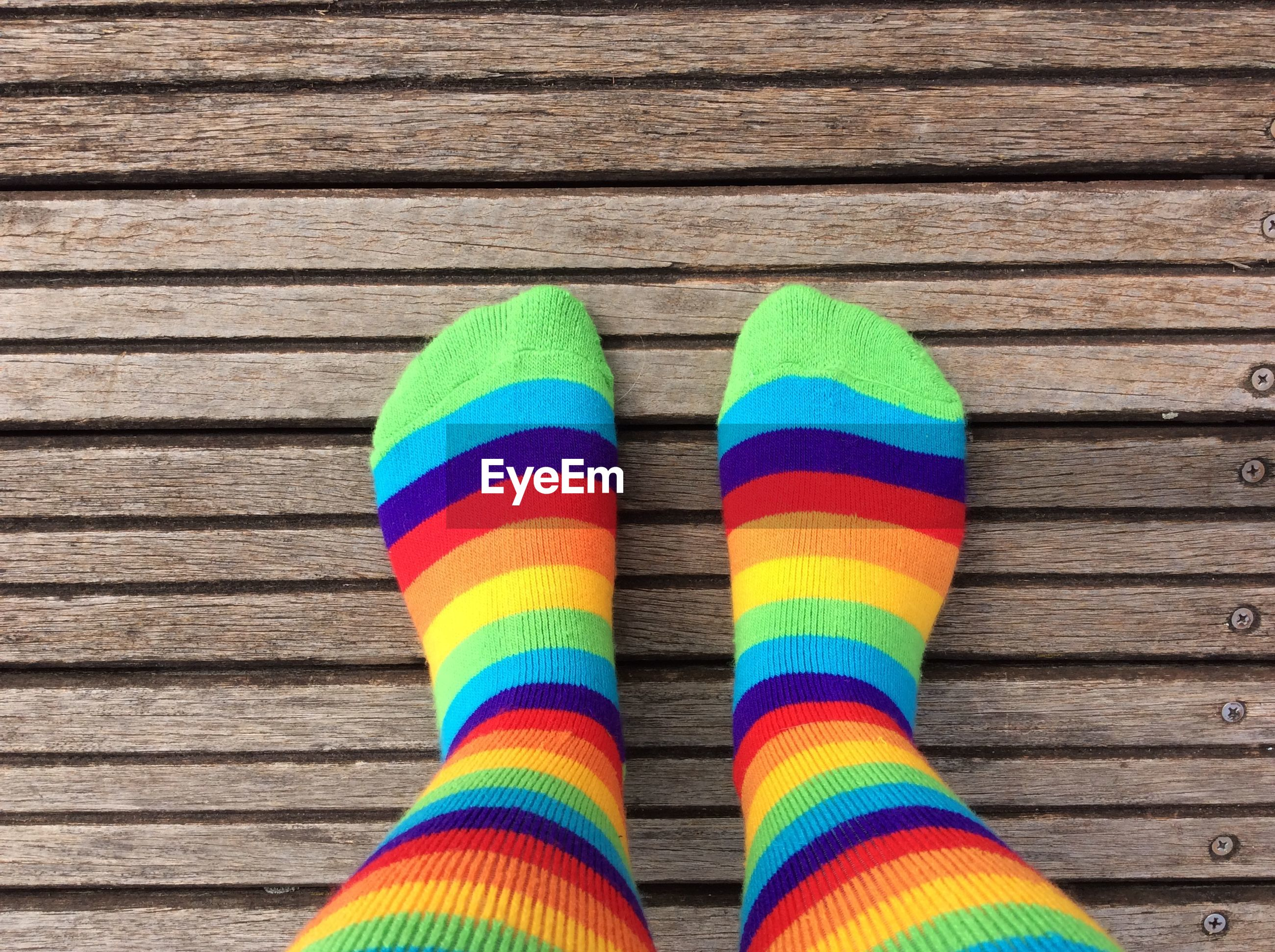 Low section of person with multi colored sock on floorboard