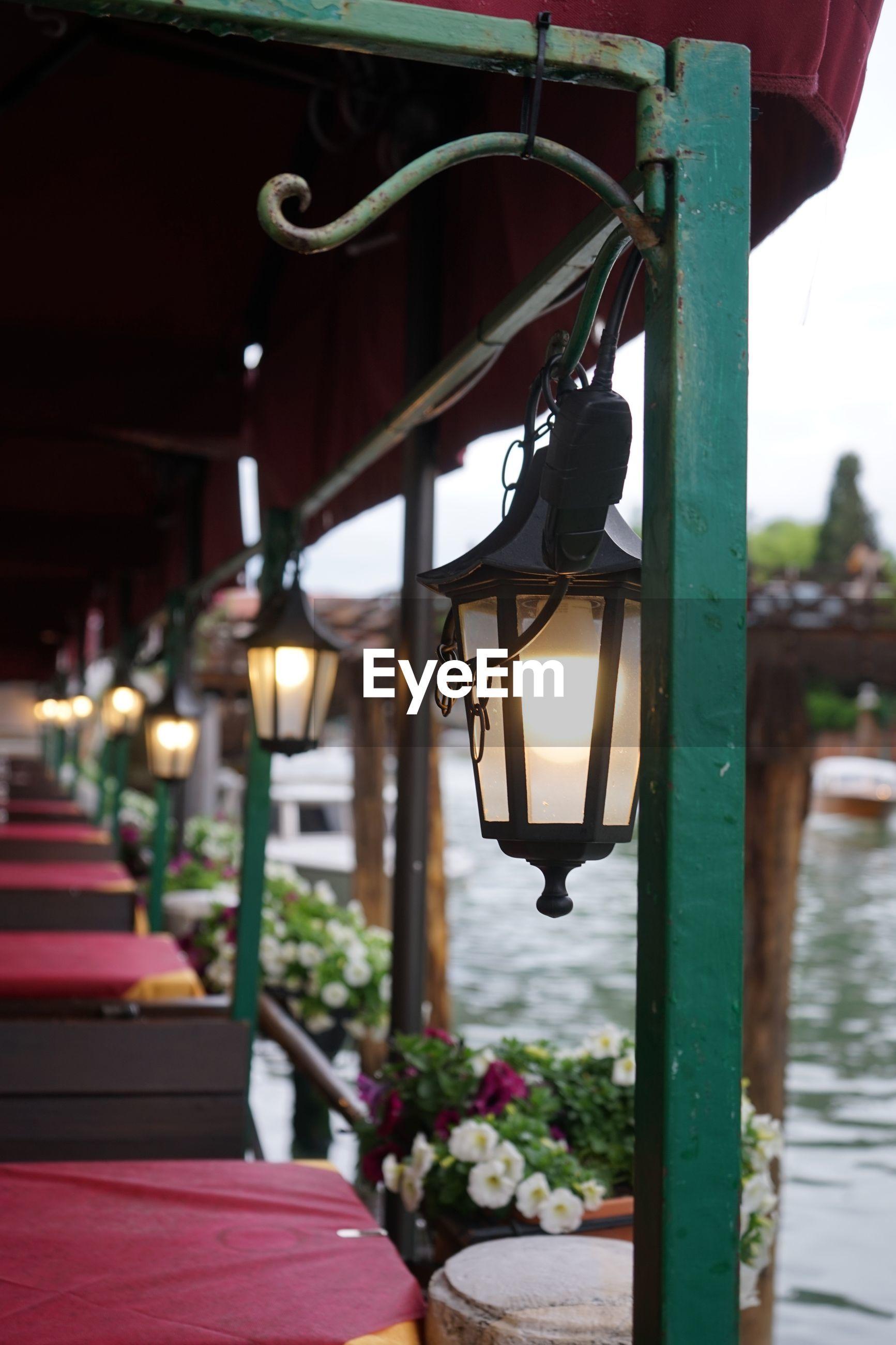 CLOSE-UP OF ILLUMINATED LAMP HANGING BY STREET LIGHT