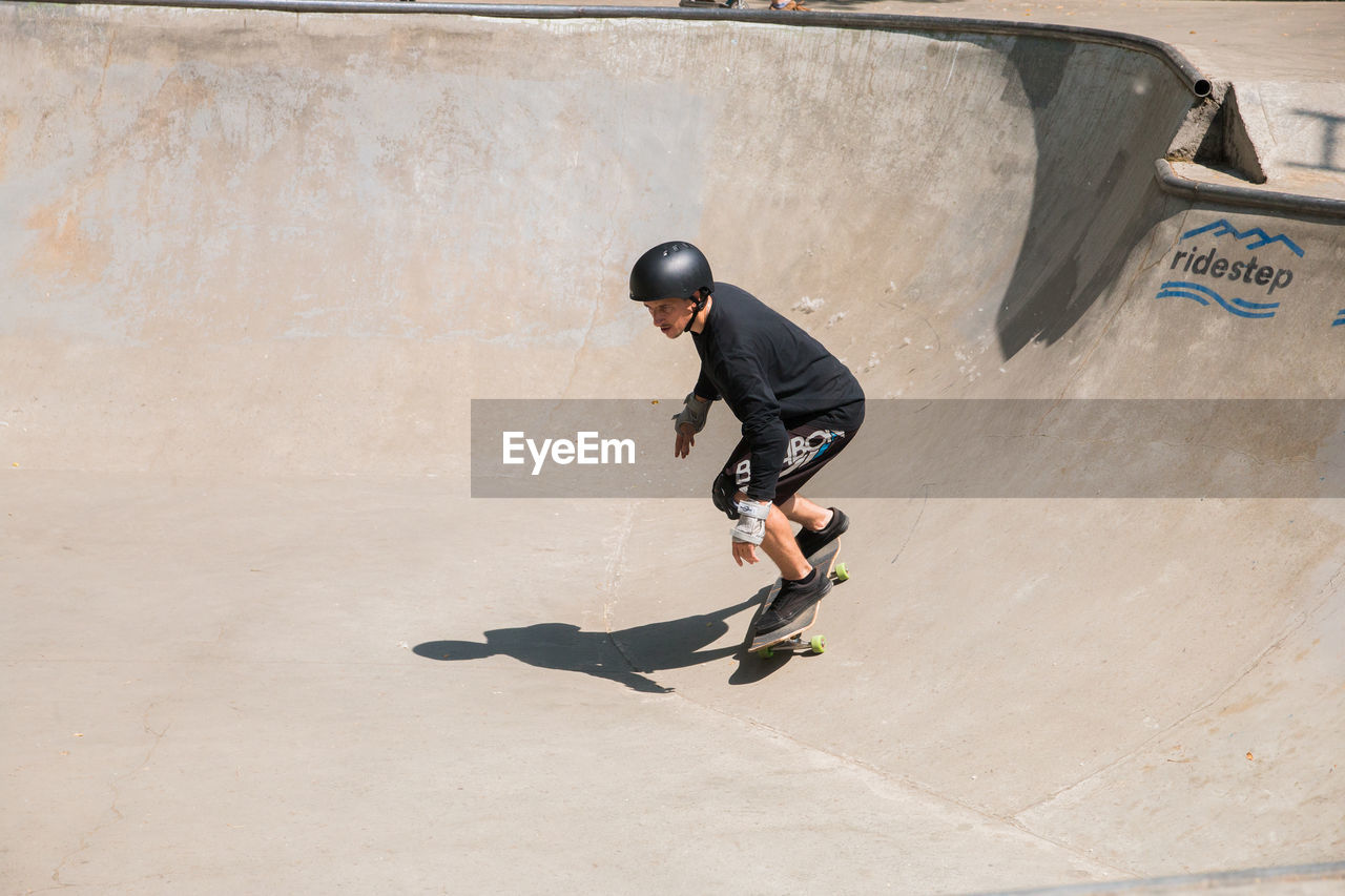 full length, one person, skateboard park, sport, skill, shadow, men, lifestyles, leisure activity, day, motion, sunlight, real people, sports equipment, skateboard, casual clothing, balance, architecture, outdoors, concrete, effort