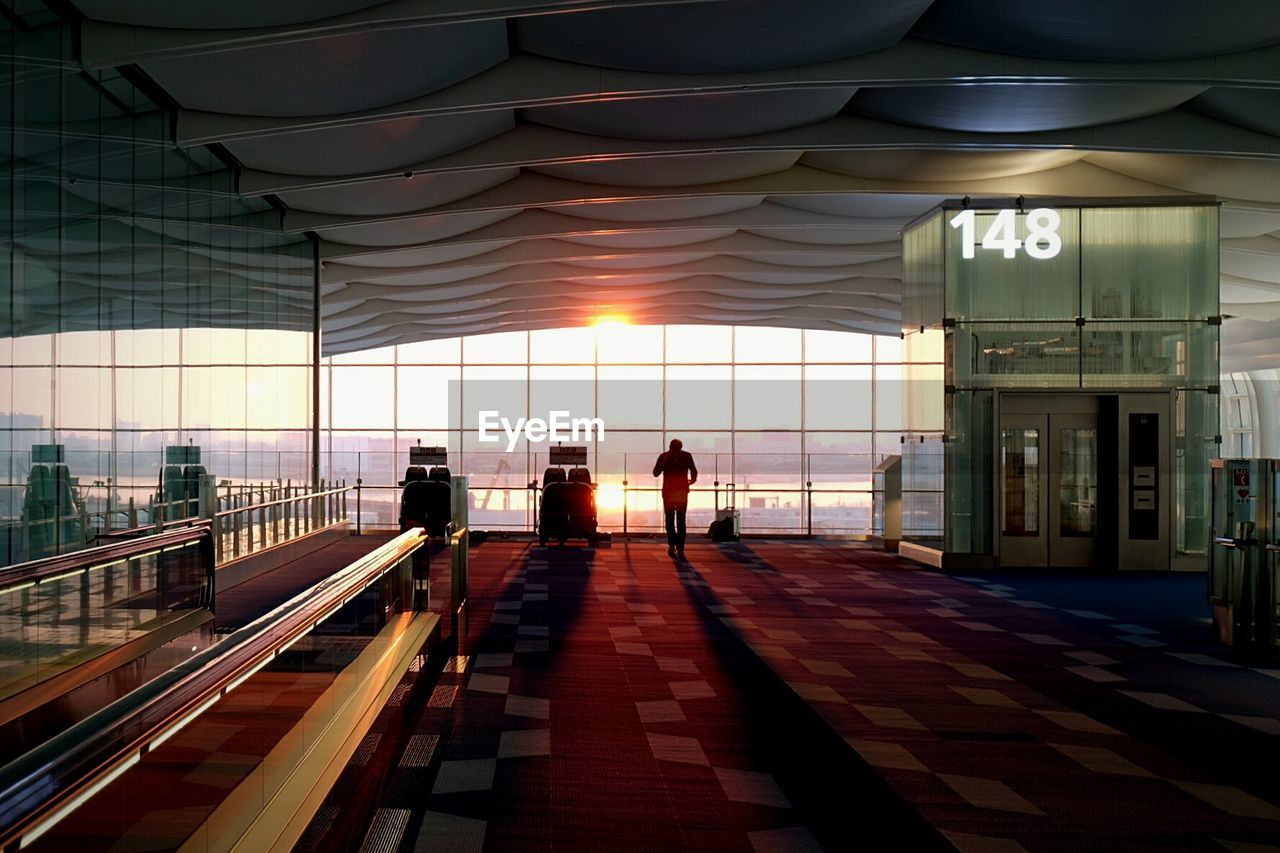Silhouette Man Standing In Departure Area At Airport During Sunset