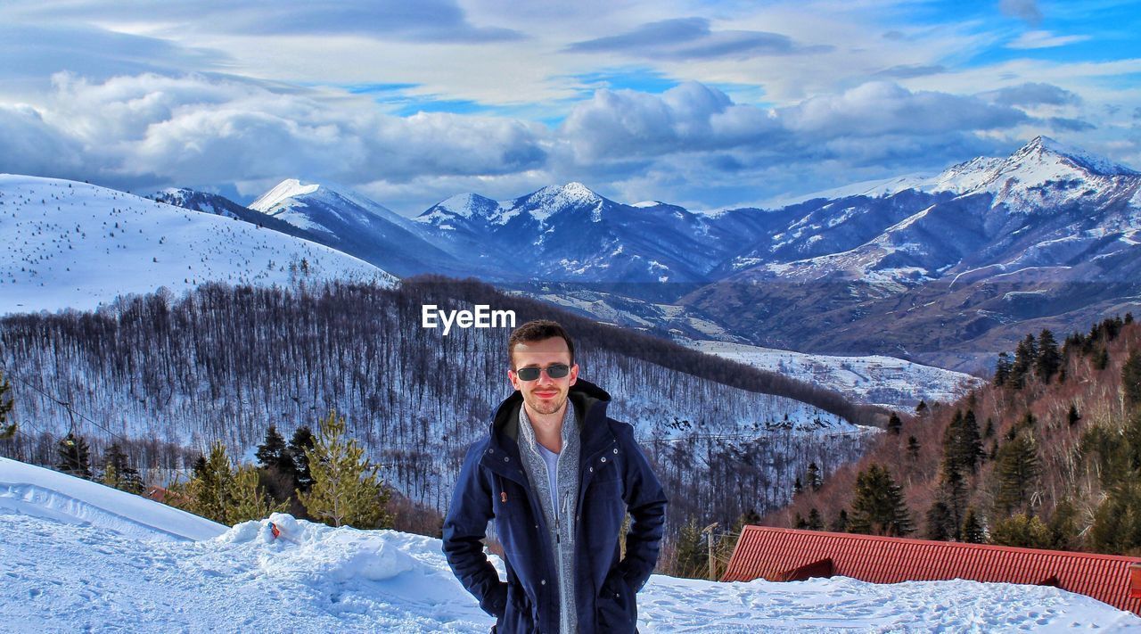 Portrait Of Woman In Sunglasses On Snowcapped Mountains Against Sky