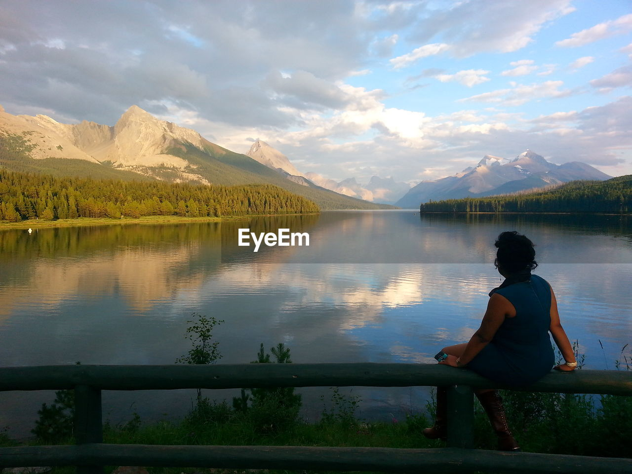 Rear View Of Woman Sitting On Railing By Lake Against Mountains