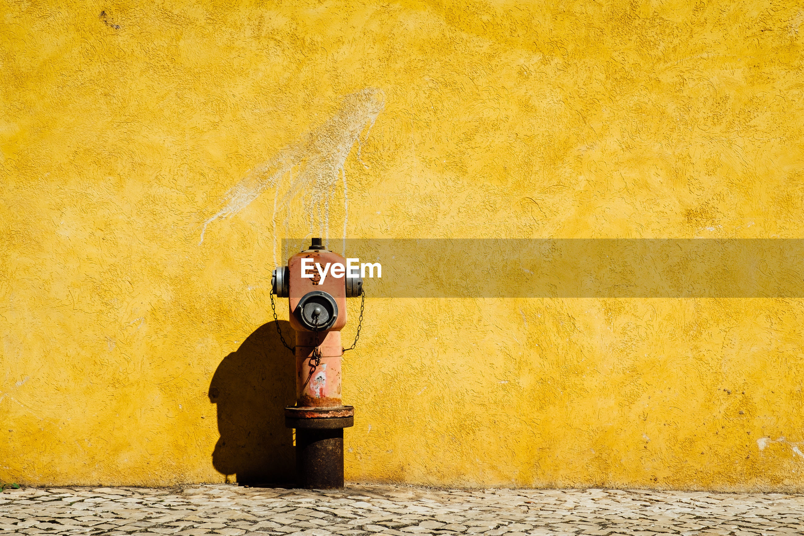 Fire hydrant on footpath by yellow wall during sunny day