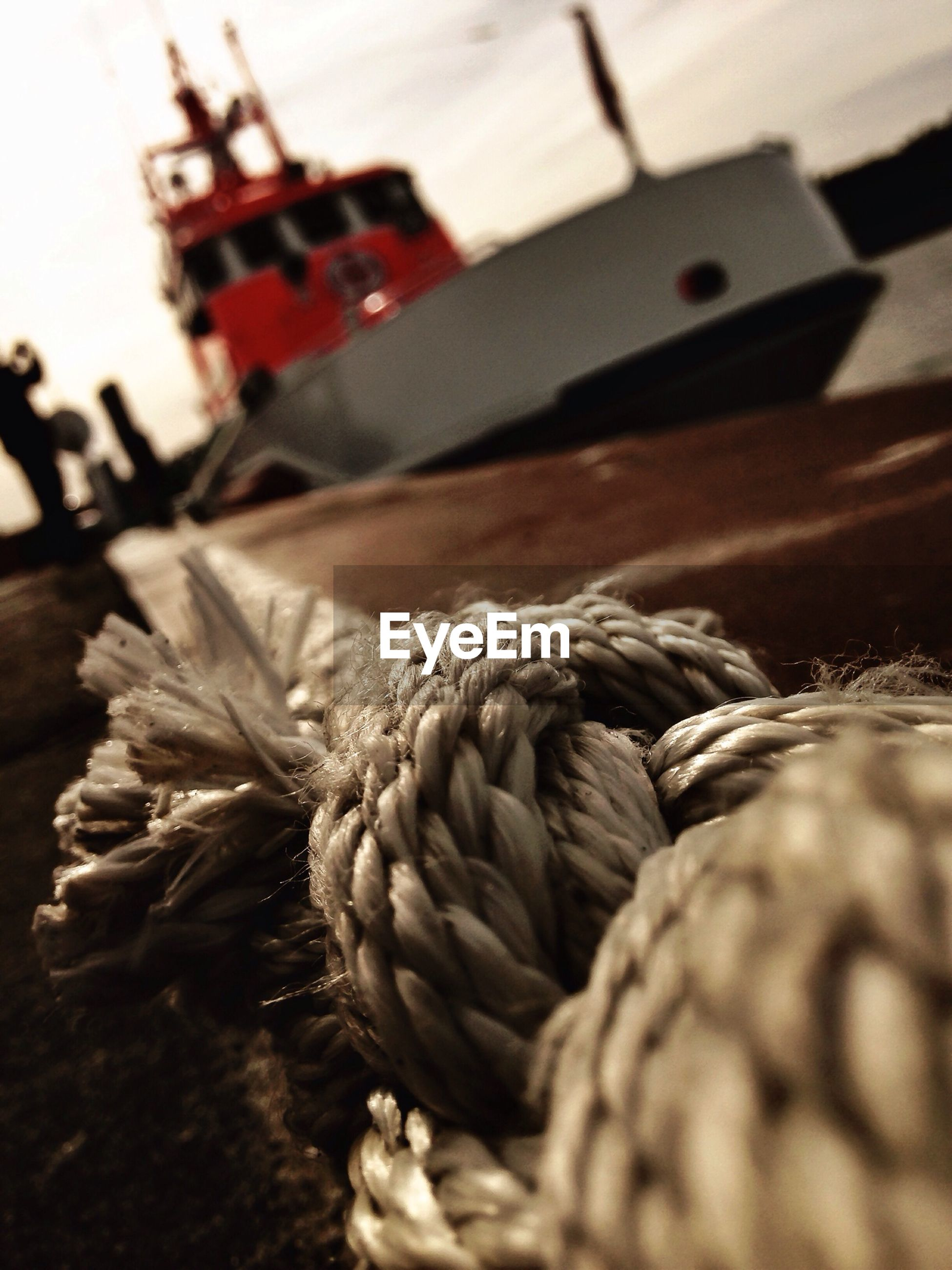 Close-up of rope against ship in harbor