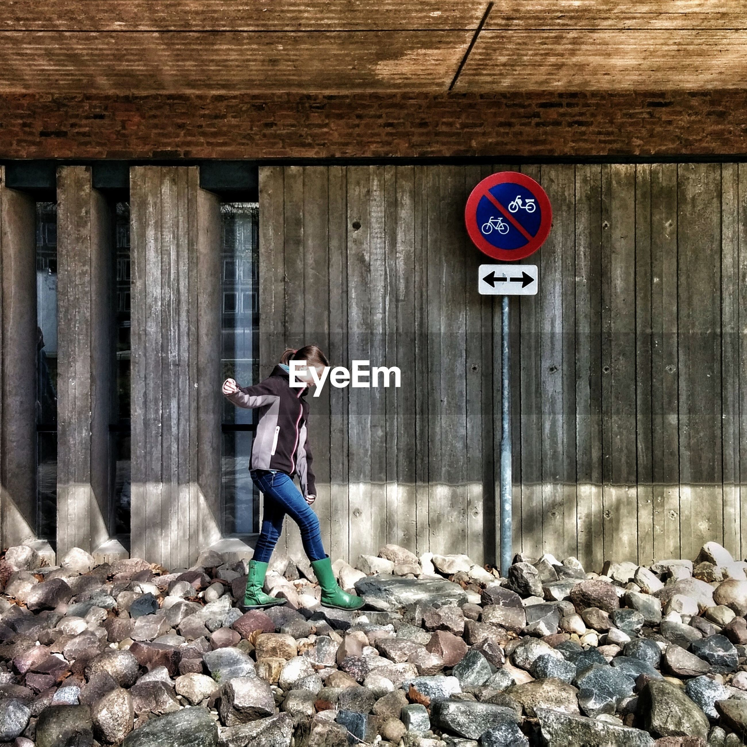 Full length of girl walking on stones by road sign against wooden wall