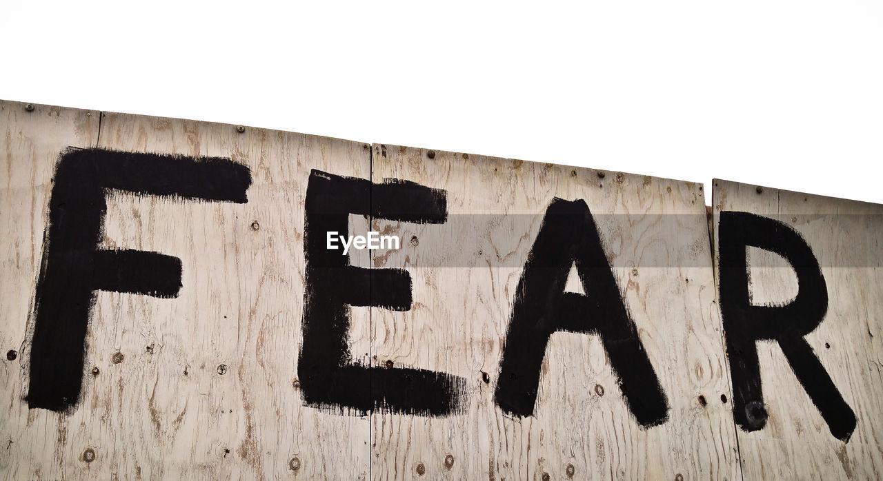 text, western script, communication, no people, capital letter, single word, architecture, day, number, wall - building feature, clear sky, built structure, low angle view, wood - material, sky, outdoors, alphabet, sign, close-up, building exterior, message