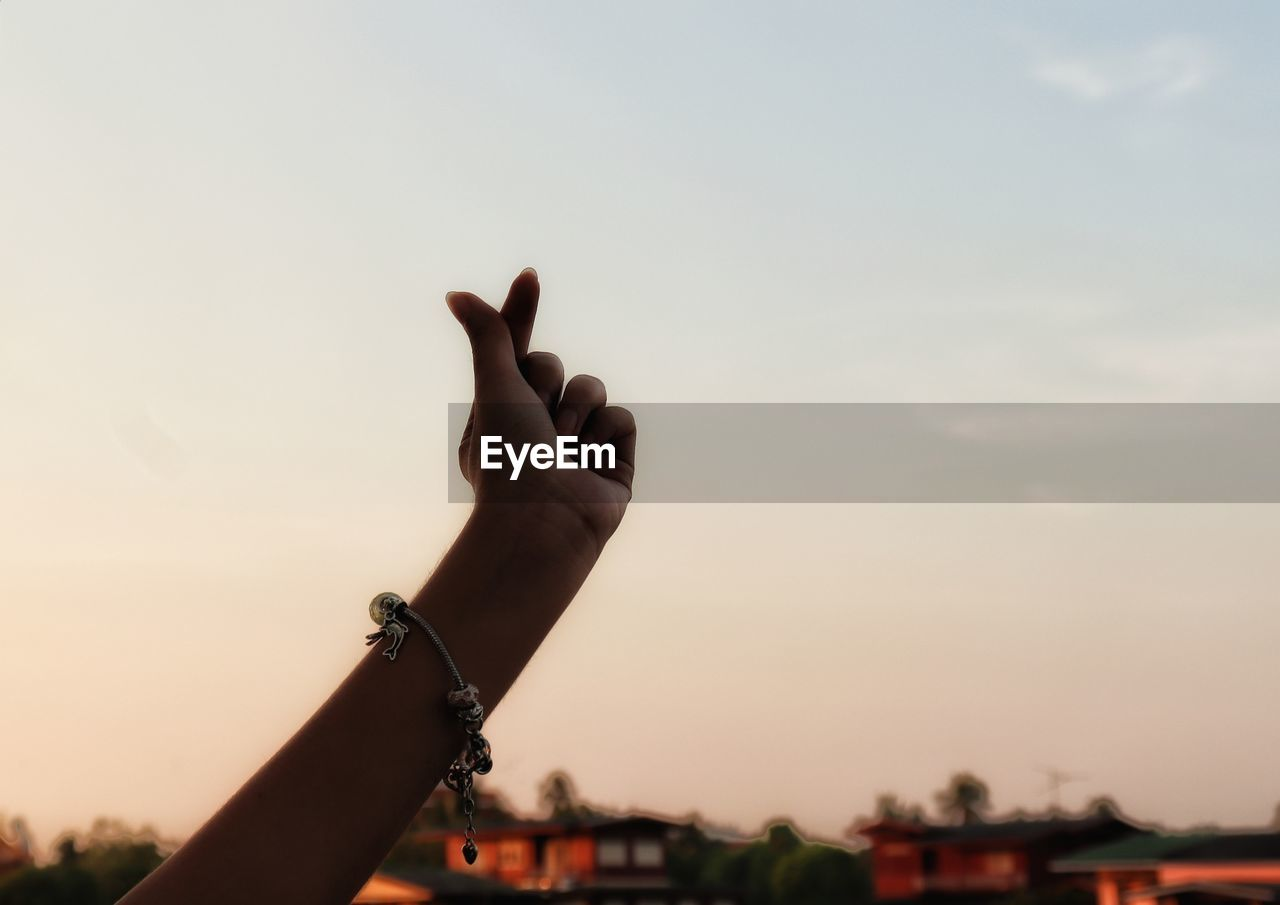 CLOSE-UP OF HAND AGAINST SKY AT SUNSET