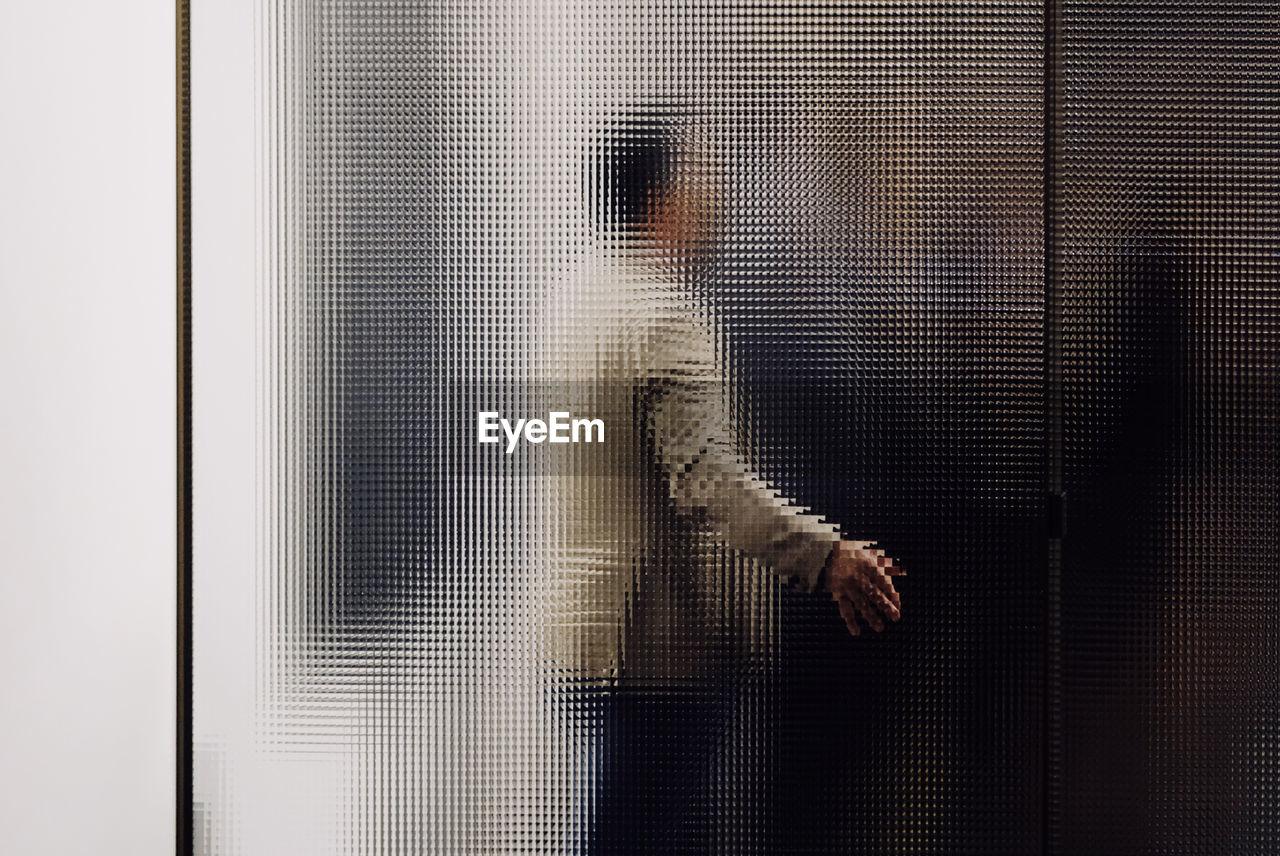 Blurred Motion Of Man Seen Through Glass Door