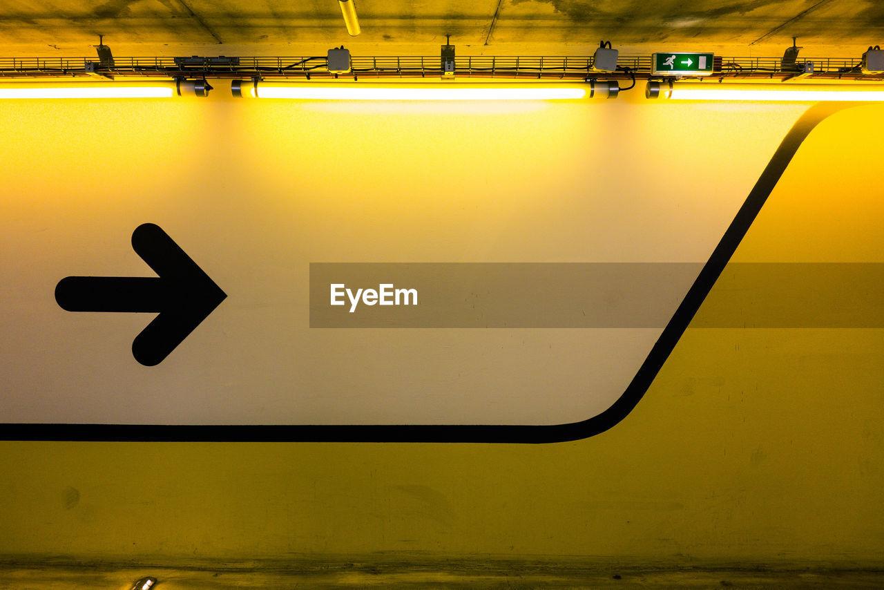 Black Arrow Symbol On Illuminated Yellow Wall