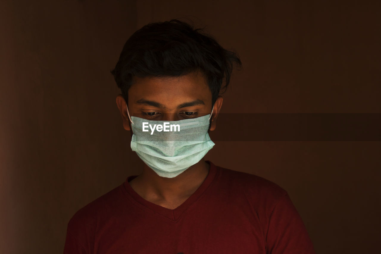 Close-up of young man wearing flu mask standing against black background