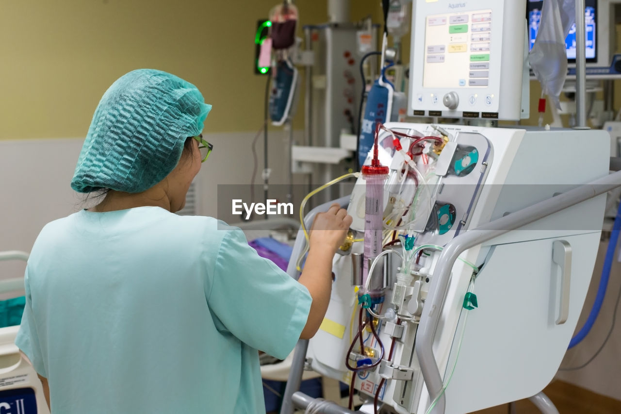 Rear view of woman operating equipment in hospital