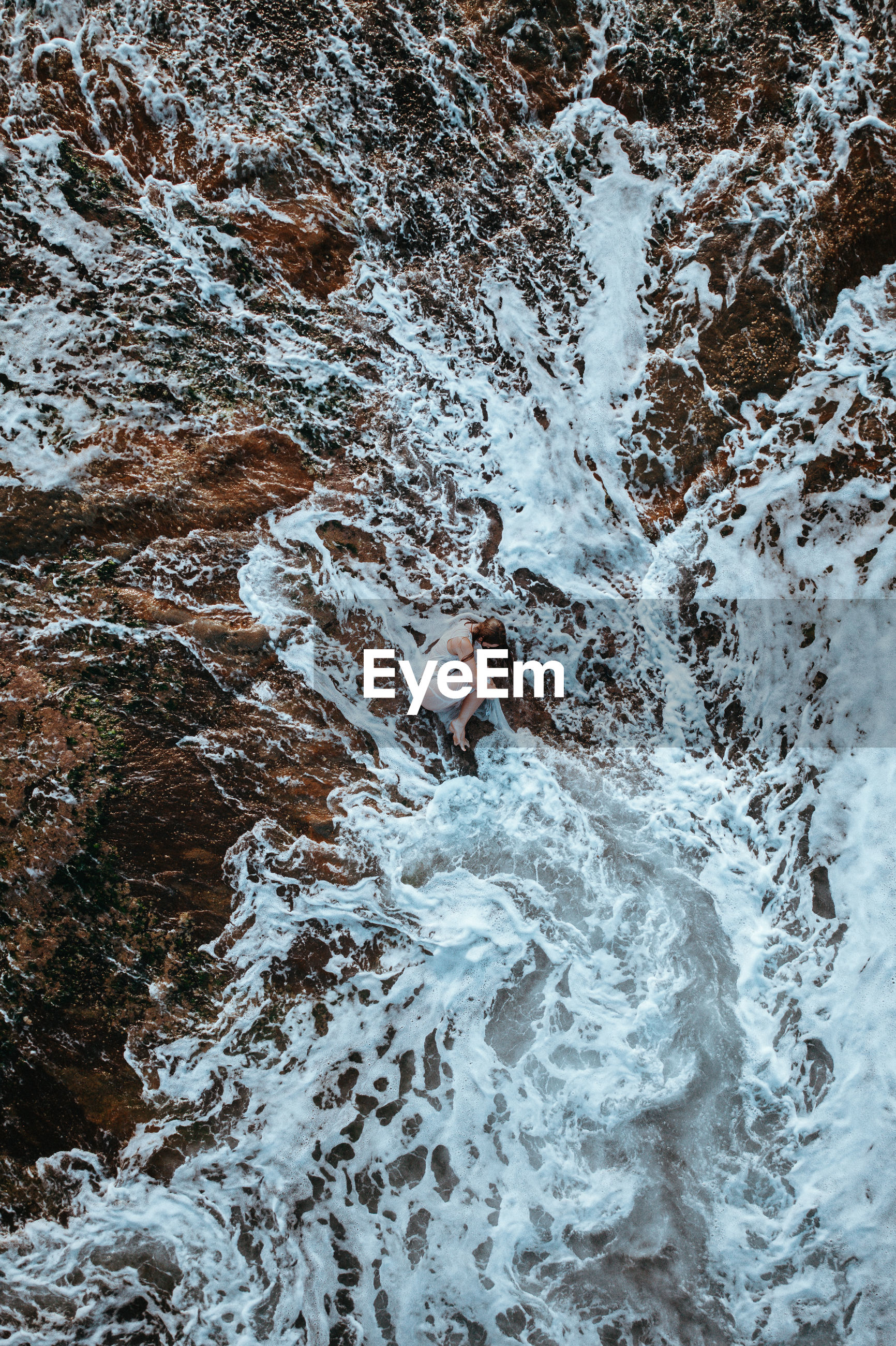 HIGH ANGLE VIEW OF WATER FLOWING OVER ROCKS