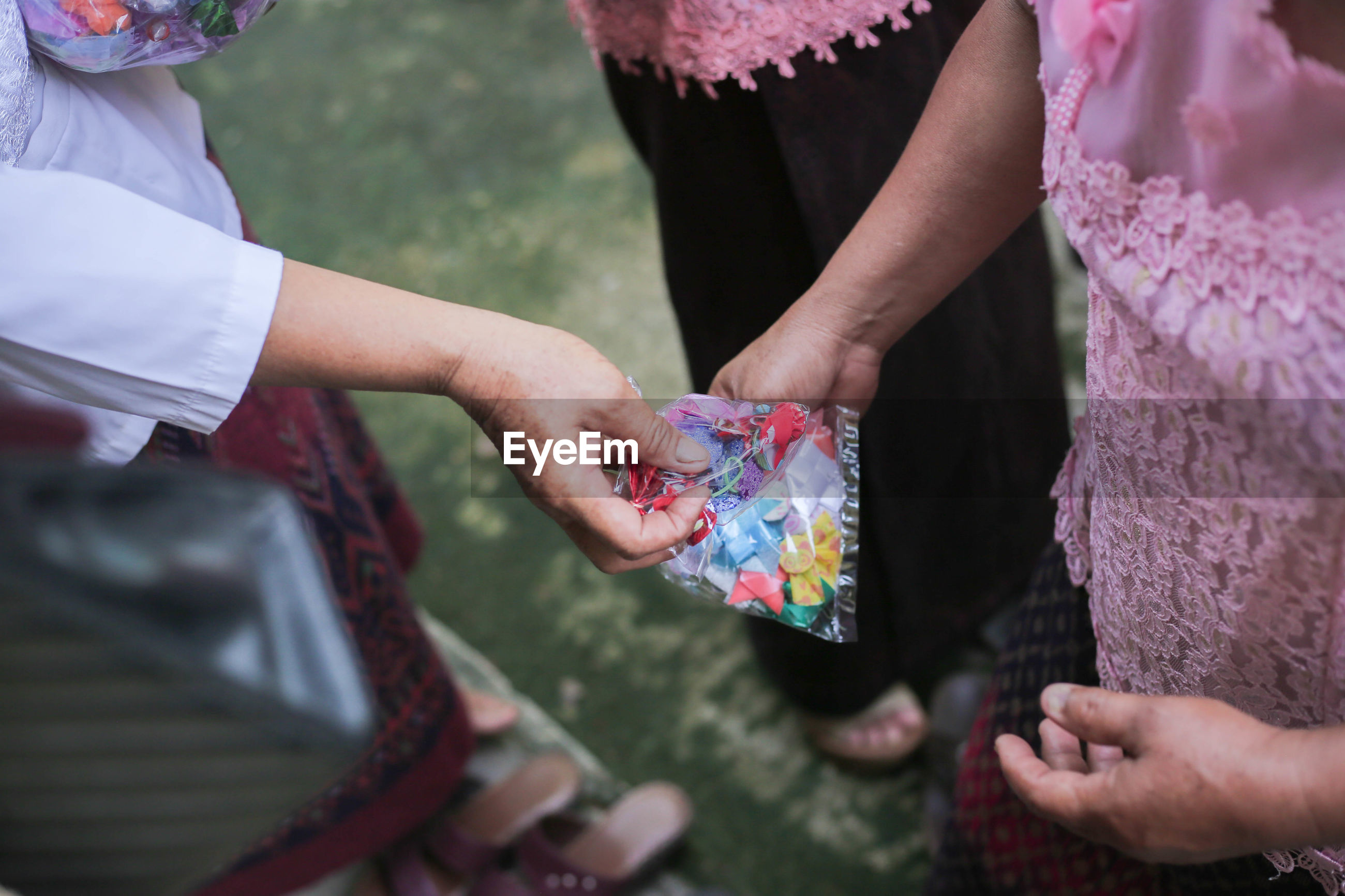 Cropped image of woman giving plastic bag to friend
