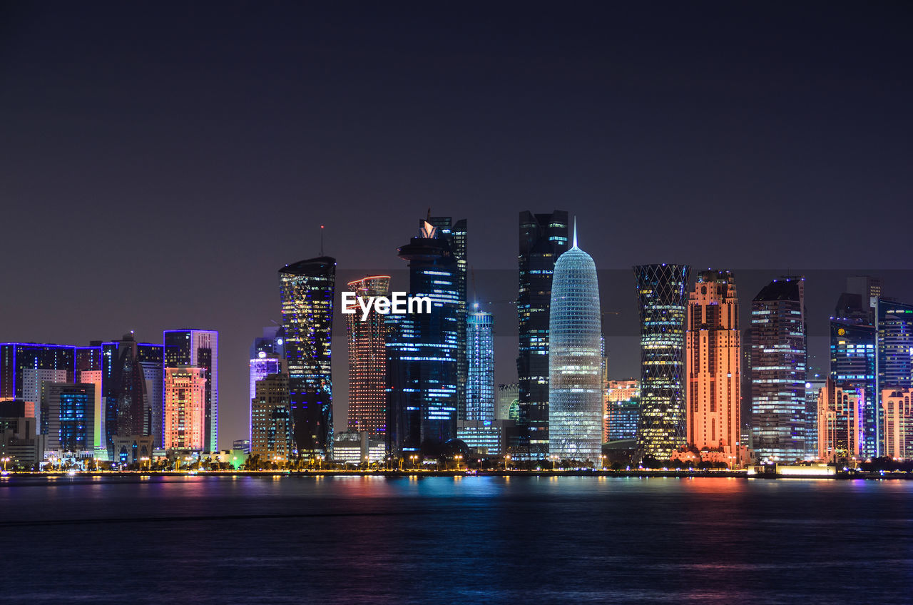 Illuminated Doha Tower And Skyscrapers By River In City Against Clear Sky At Night