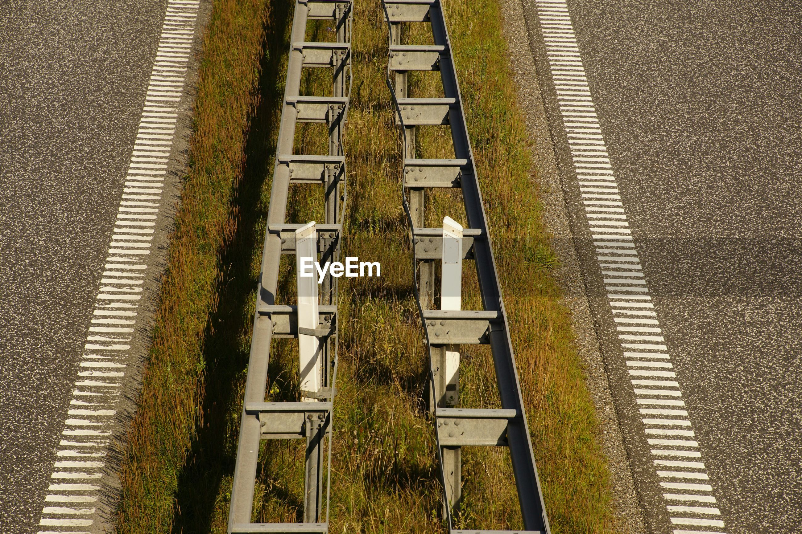 High angle view of railing on grass amidst highway