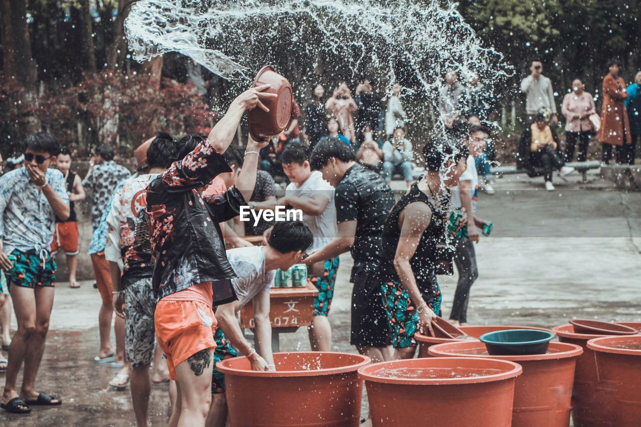 group of people, water, crowd, real people, motion, splashing, men, fun, enjoyment, wet, spraying, day, standing, women, city, nature, people, architecture, outdoors
