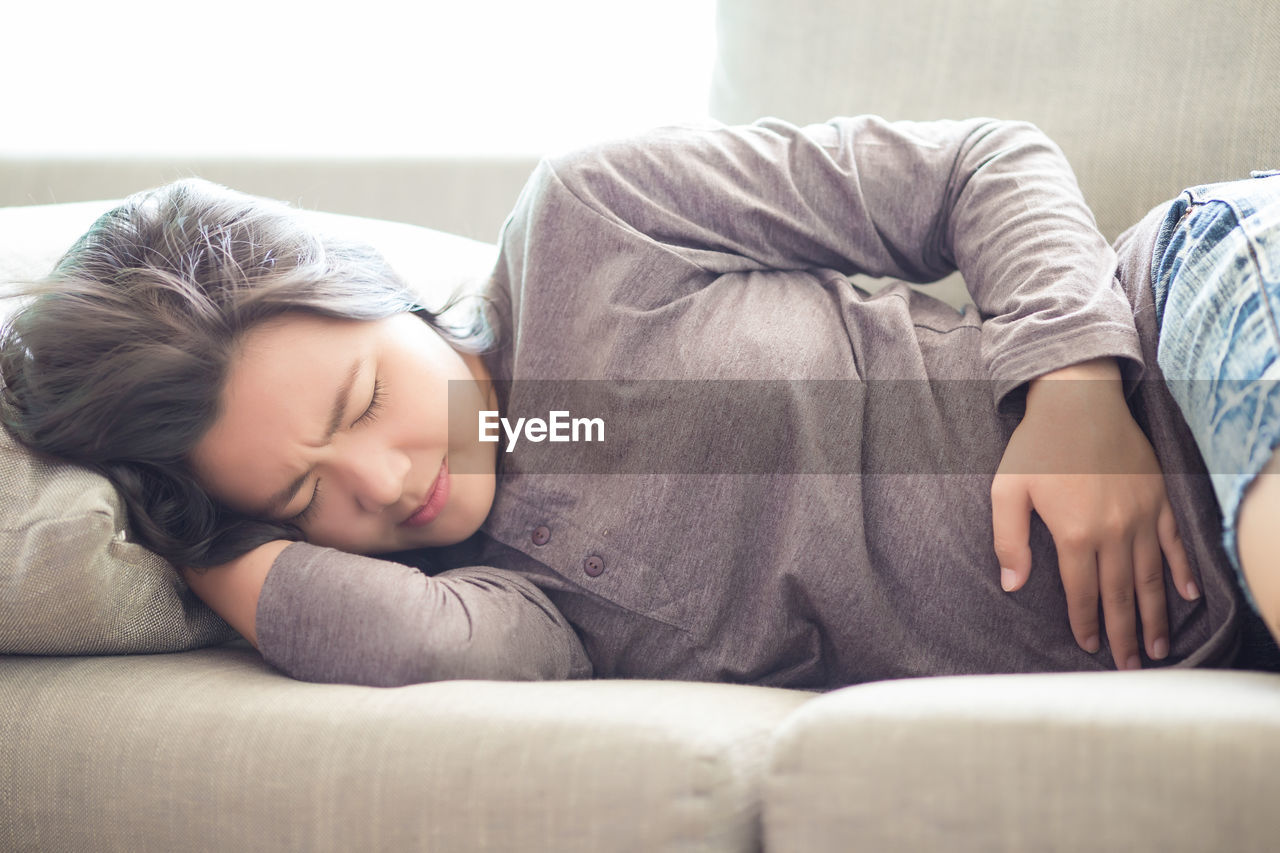 Young woman suffering from stomachache while sleeping on sofa at home