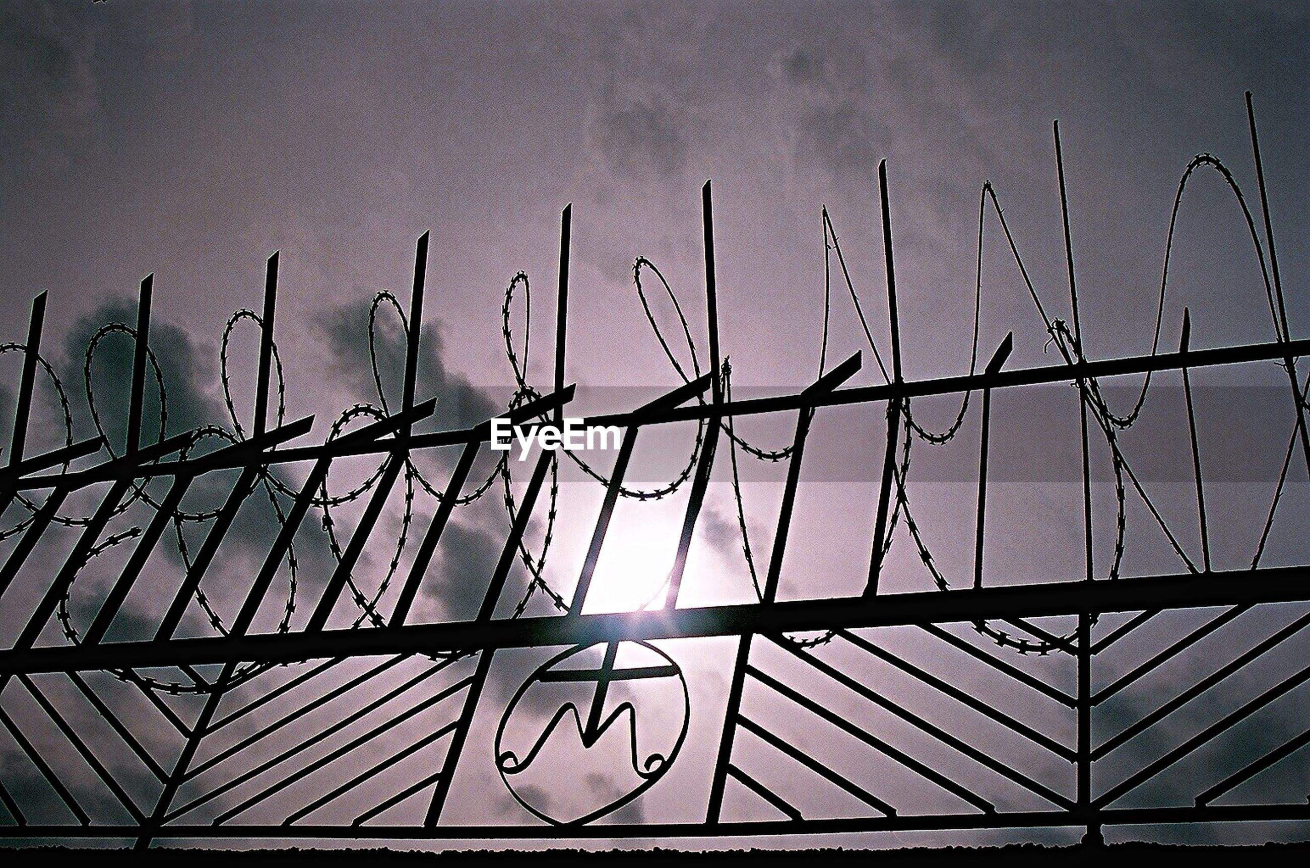 text, metal, low angle view, fence, western script, communication, barbed wire, safety, chainlink fence, protection, close-up, metallic, sky, no people, outdoors, day, pattern, security, connection, bird