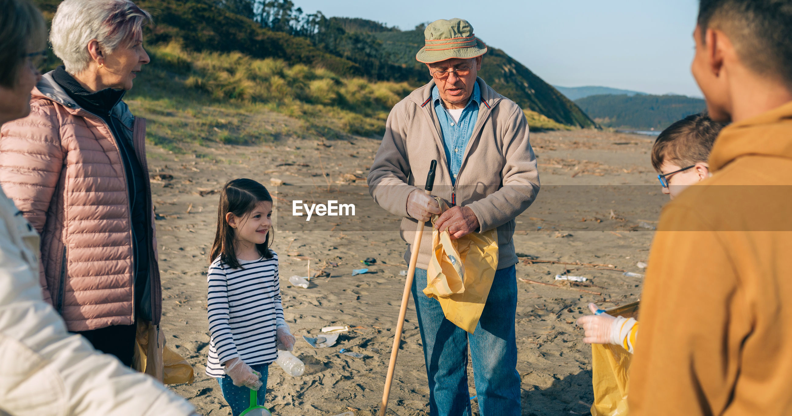 Grandparents and grandchildren cleaning while standing at beach
