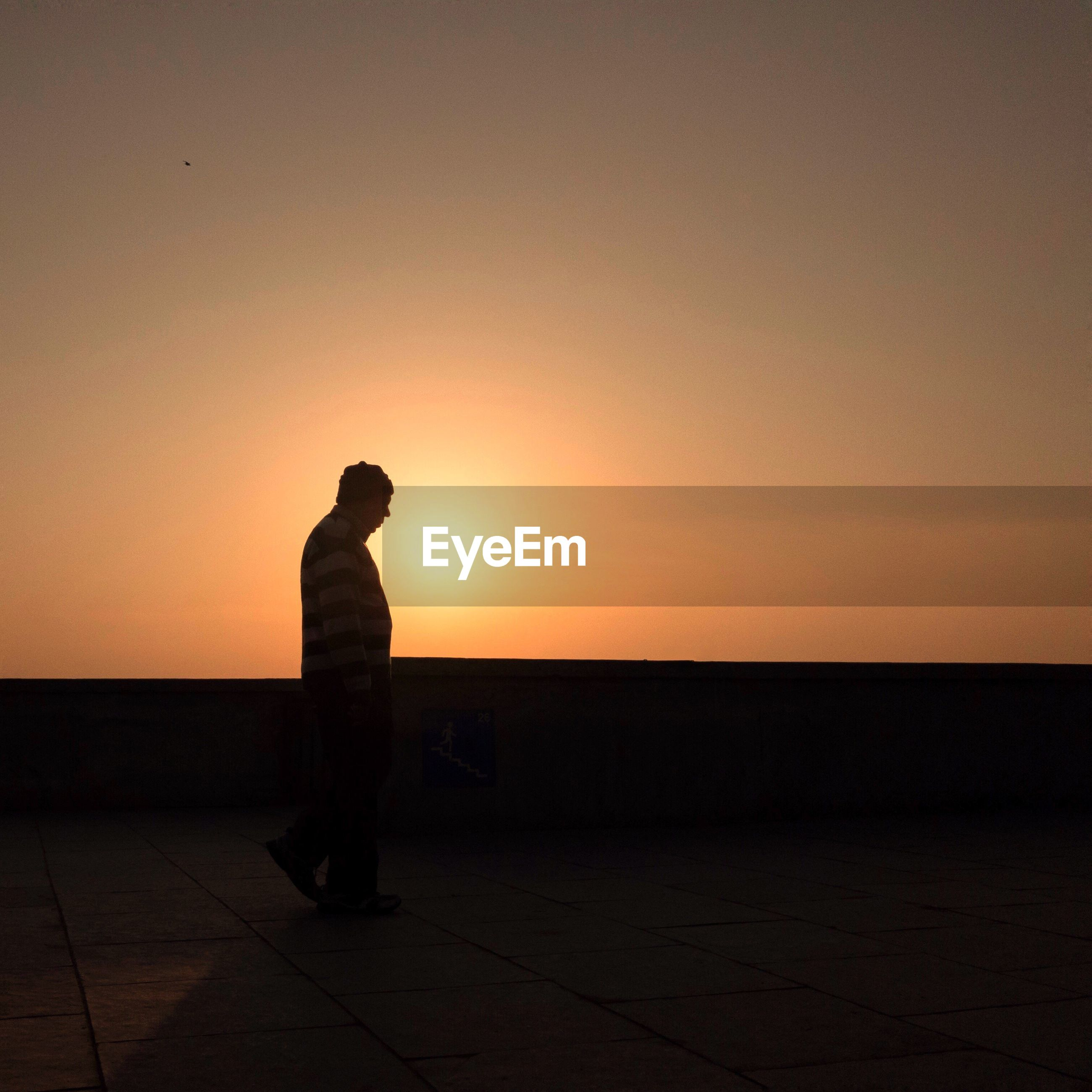 Side view of silhouette man walking on promenade against clear sky during sunset