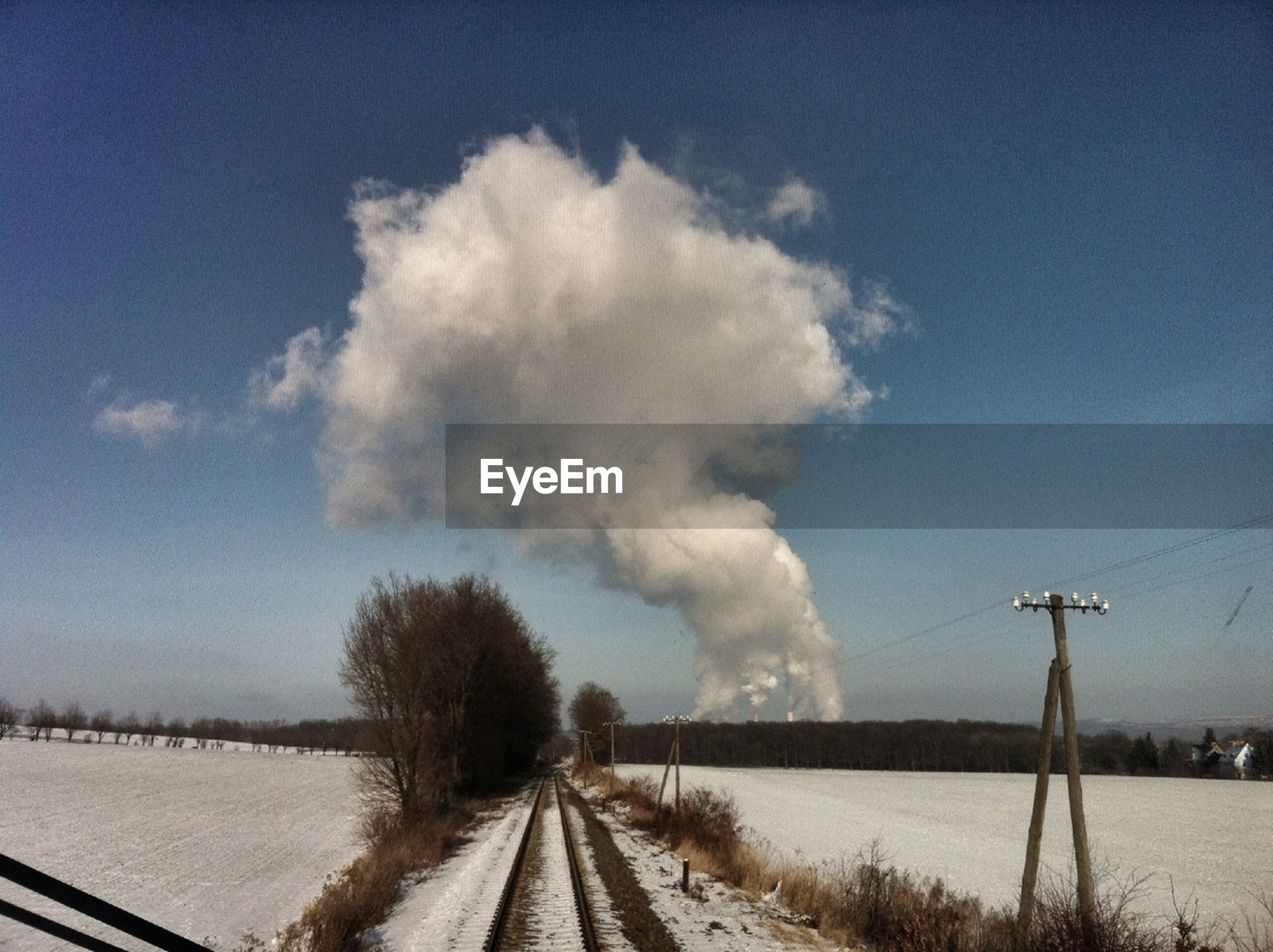 Factories emitting smoke seen through train windshield
