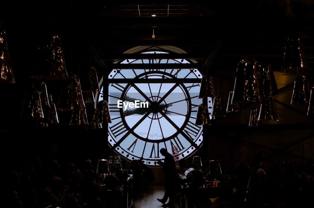 indoors, architecture, group of people, built structure, clock, time, real people, roman numeral, museum, incidental people, men, day, illuminated, shape, roman, standing, women, clock face, lighting equipment, adult, ceiling