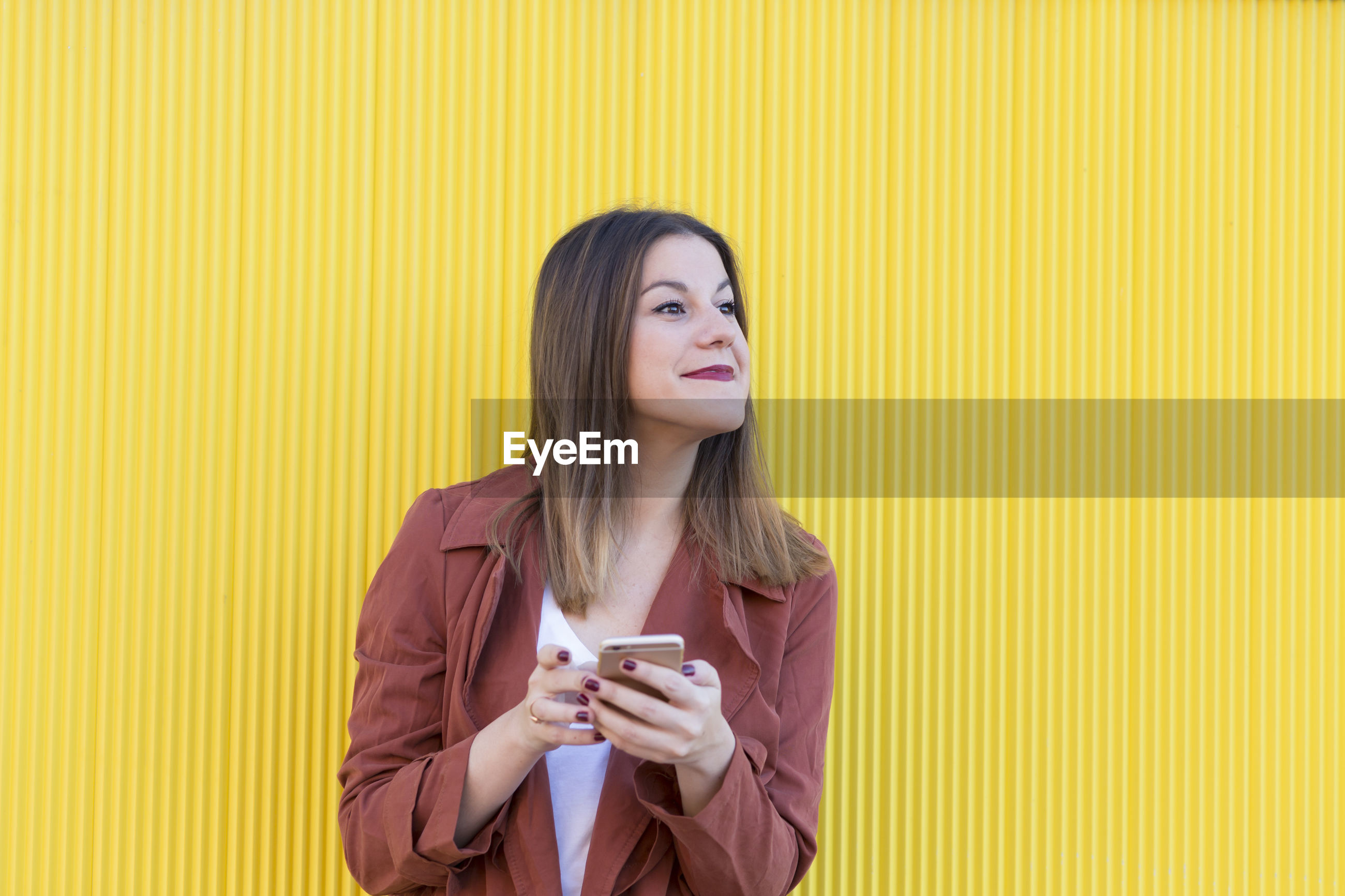 Fashionable young woman using mobile phone while looking away against yellow wall