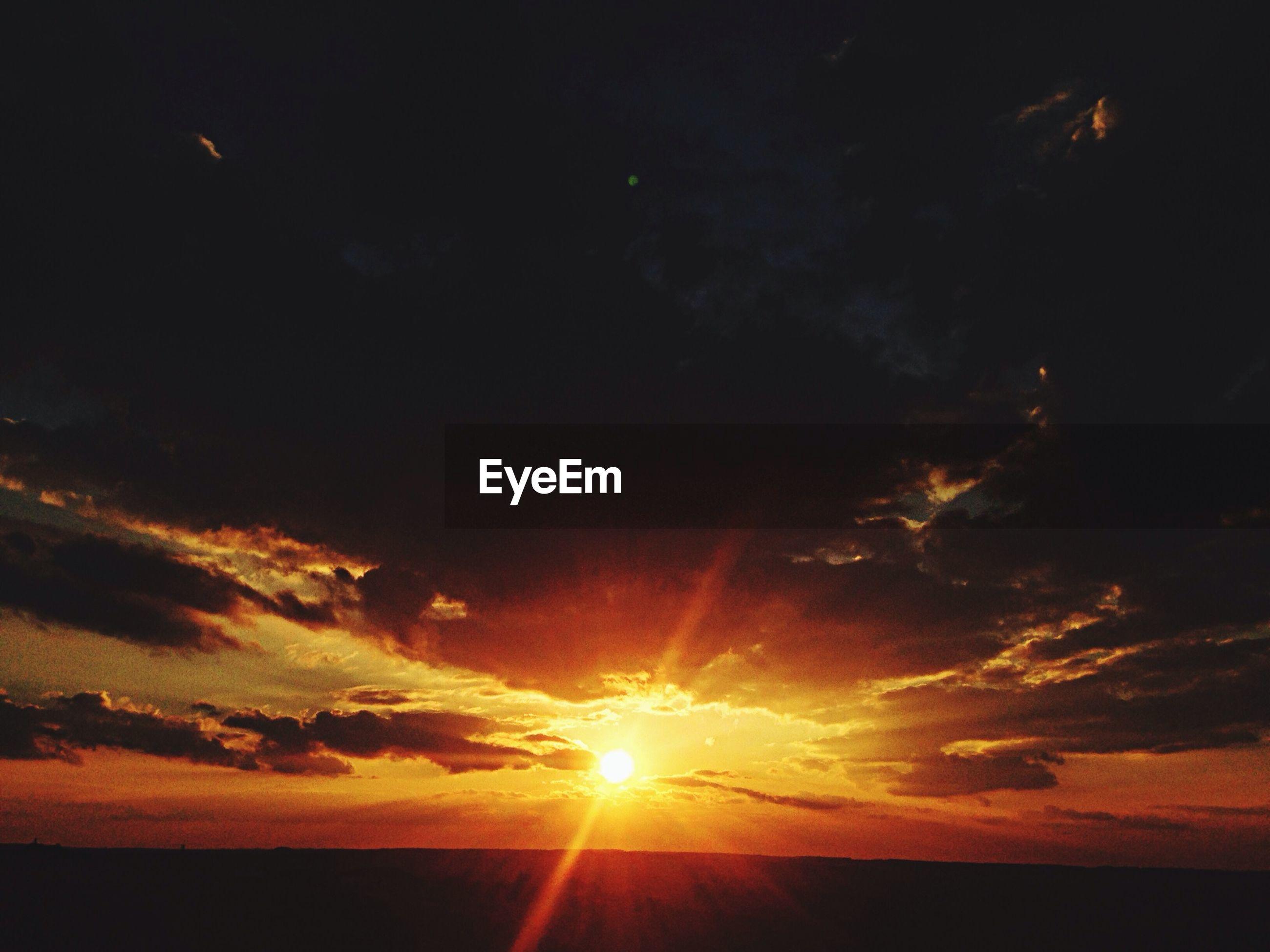 sunset, sun, scenics, tranquil scene, beauty in nature, tranquility, sky, silhouette, nature, idyllic, orange color, sunlight, sunbeam, landscape, cloud - sky, outdoors, dark, dramatic sky, low angle view, no people
