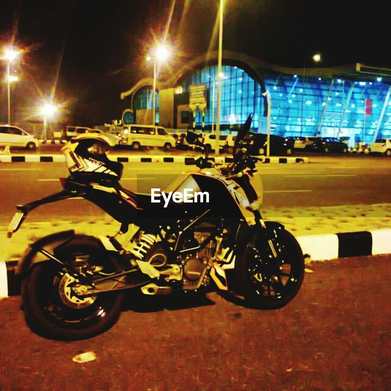 transportation, land vehicle, night, motorcycle, mode of transport, illuminated, street, built structure, outdoors, stationary, helmet, building exterior, men, scooter, one person, sports race, people