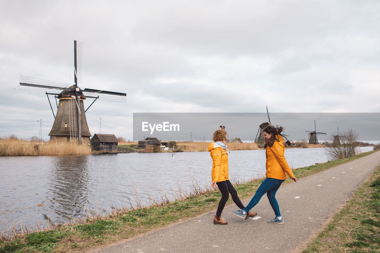 Two girls jumping agains traditional windmill