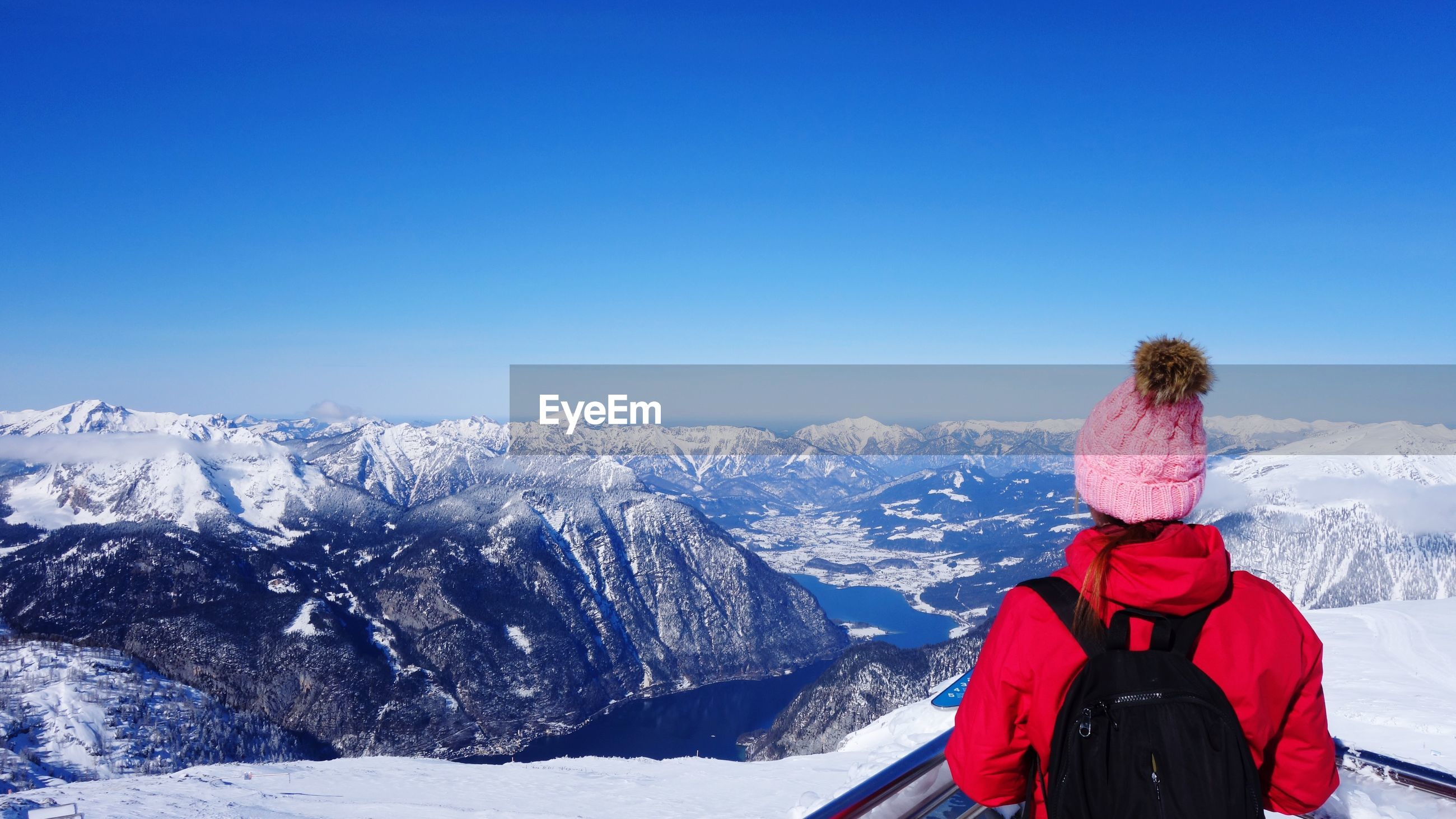 Rear view of woman looking at snowcapped mountains against clear blue sky
