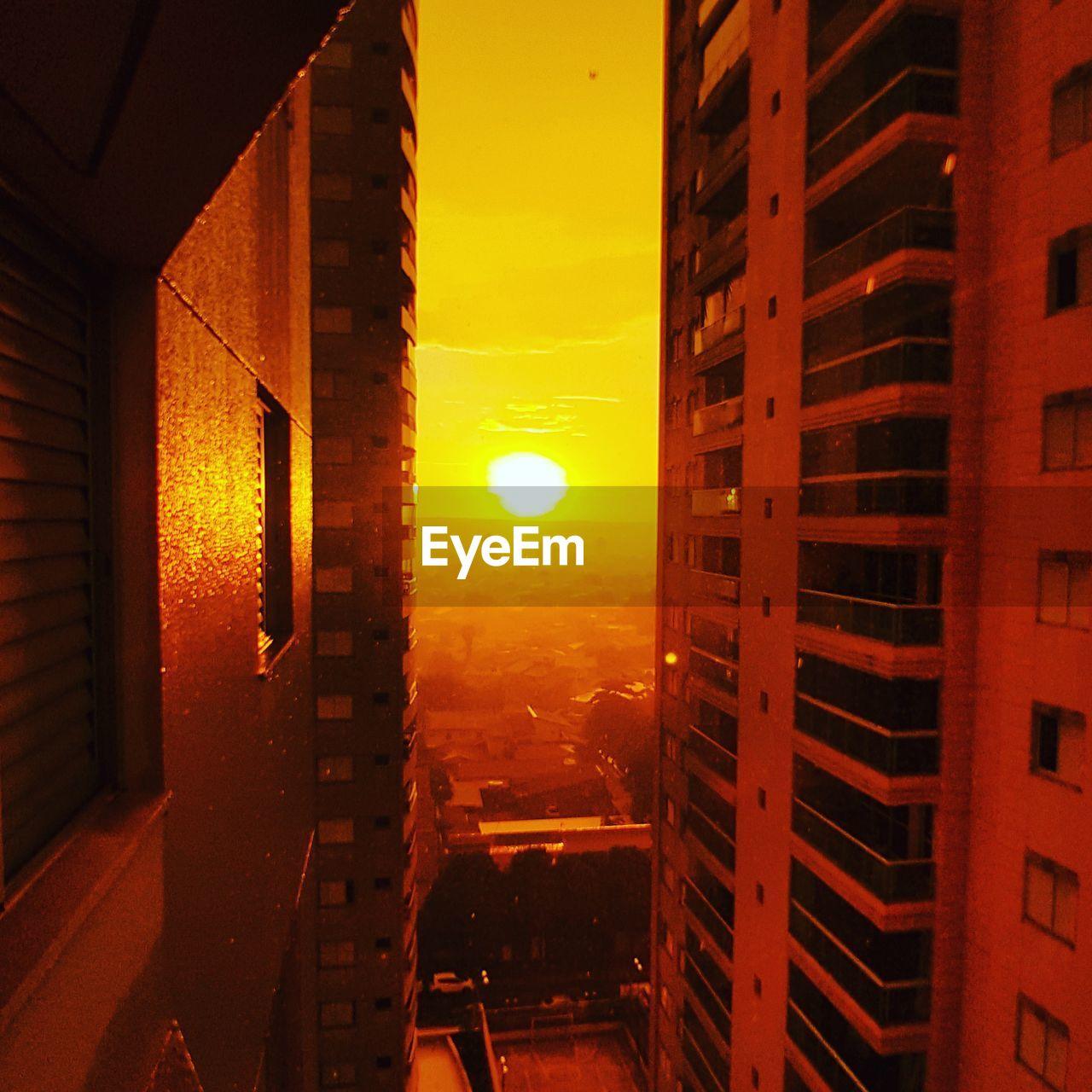 sunset, orange color, architecture, sun, building exterior, built structure, no people, sky, sunlight, outdoors, yellow, scenics, city, nature