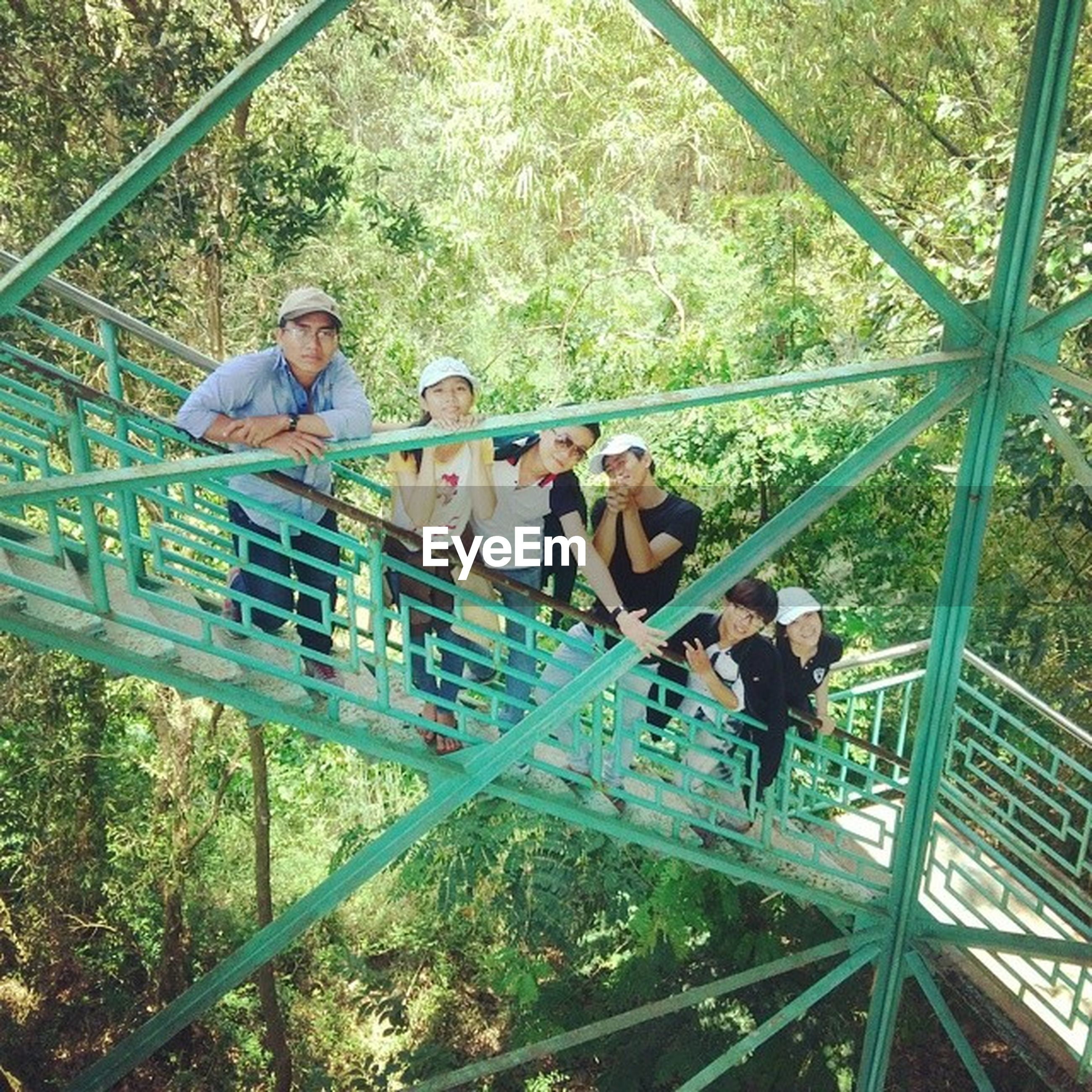 lifestyles, leisure activity, casual clothing, railing, men, togetherness, full length, tree, person, childhood, boys, transportation, high angle view, bonding, standing, connection, elementary age