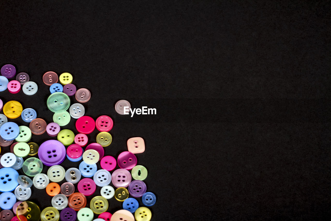 Close-up of multi colored buttons over black background