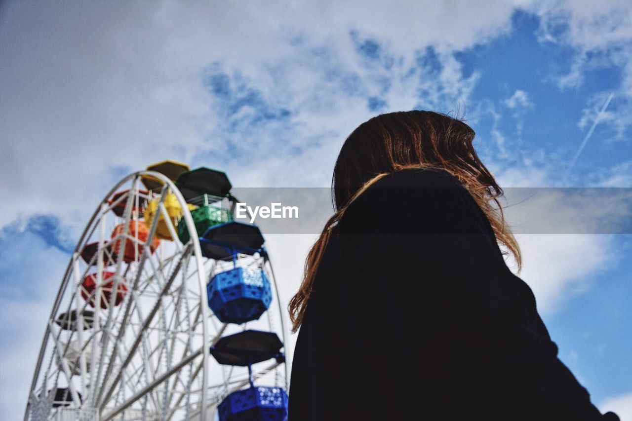Low Angle View Of Woman And Ferris Wheel Against Sky