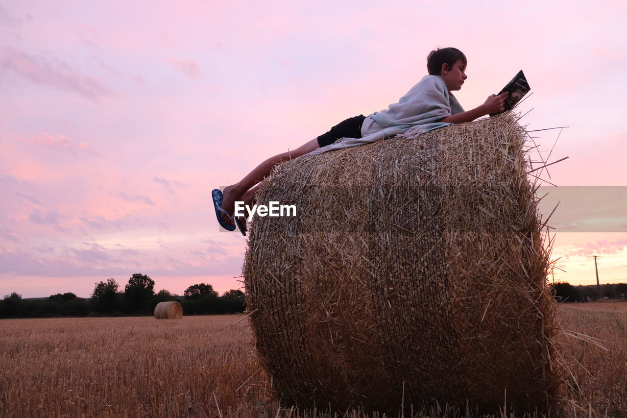 Boy using digital tablet on hay against sky during sunset