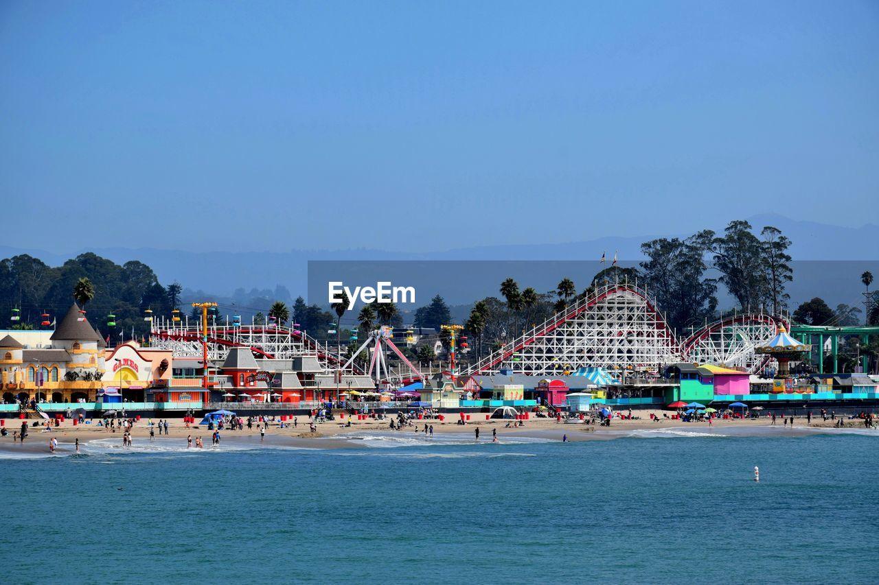 Amusement Park At Beach Against Clear Blue Sky